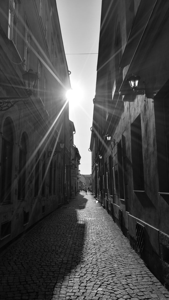 architecture, built structure, building exterior, the way forward, cobblestone, outdoors, sunlight, sky, no people, city, day