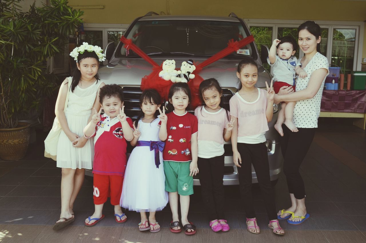 looking at camera, full length, portrait, girls, boys, childhood, standing, medium group of people, real people, smiling, elementary age, cheerful, togetherness, happiness, friendship, day, lifestyles, outdoors, women, child, young adult, young women, people