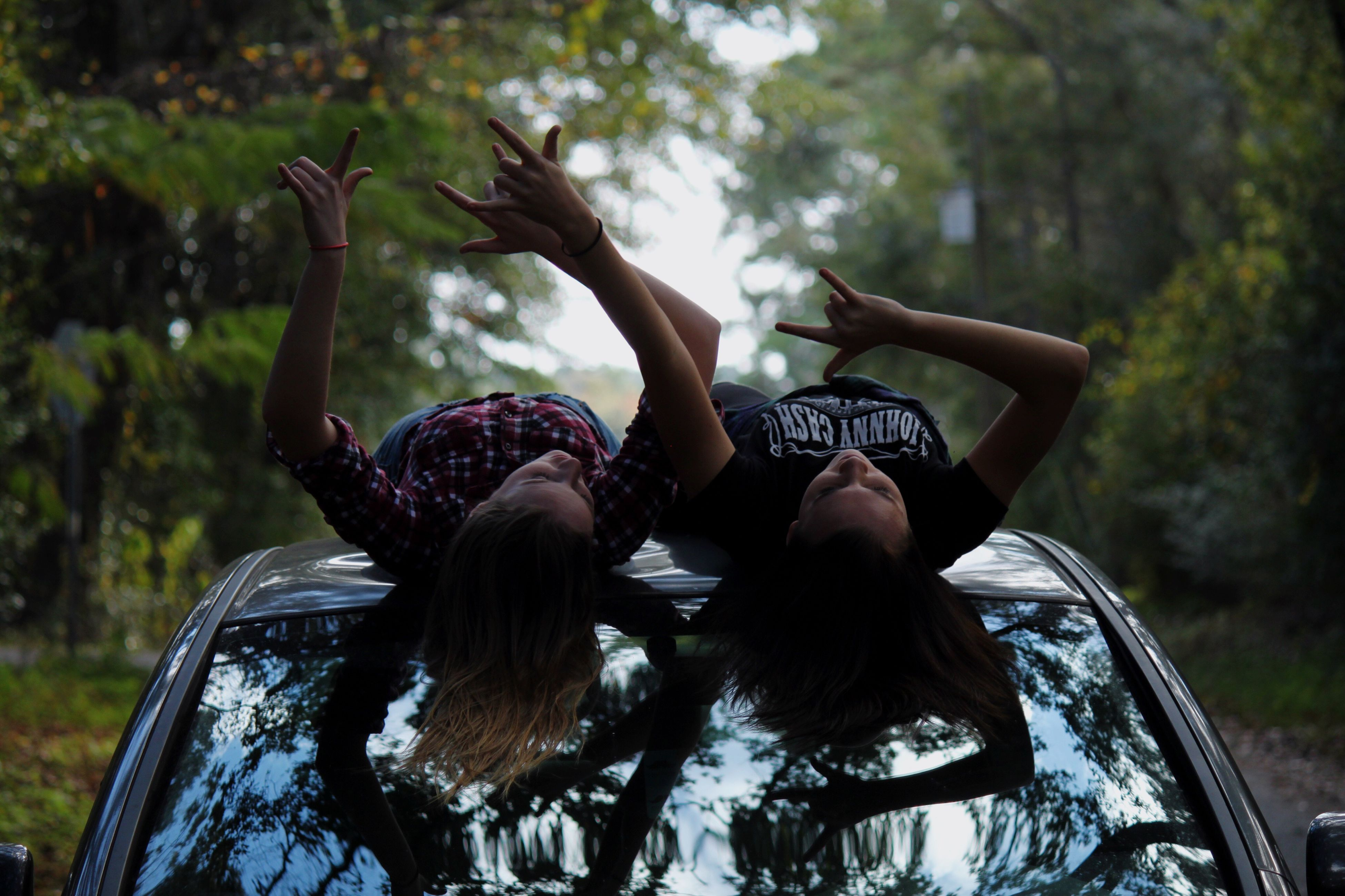 two people, long hair, carefree, young adult, adults only, people, happiness, togetherness, fun, only women, sitting, friendship, adult, women, bonding, tree, outdoors, cheerful, young women, day, human body part