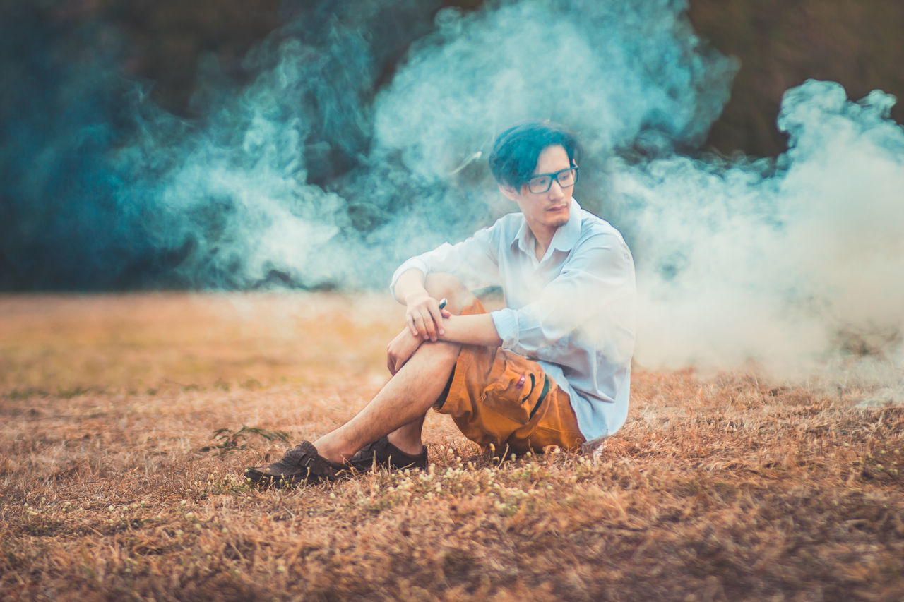 """""""Love is like the wind, you can't see it but you can feel."""" smoke color Colors Man Adult Adults Only Art Colorful Full Length Grass Landscape Lifestyles Night One Person Outdoors People Sitting Smoke - Physical Structure Smoke Color Weapon Young Adult Young Women"""