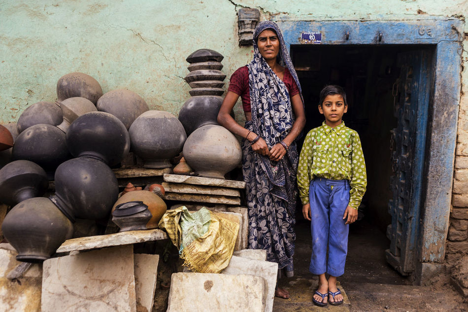 A mother and son pose outside the family home in Ujjain, India Boy Documentary Photography Environmental Portraits Flipflops Full Length Home India Looking At Camera Mother Mum Outdoor Photography Outdoors Outside Outside Photography Portrait Pots Real People Rural Scene Son Two People Ujjain