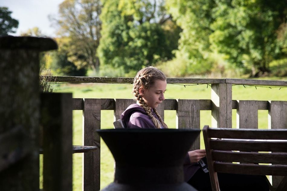 Child reading on holiday in the countryside One Person Looking Down Young Adult Lifestyles Railing Outdoors Only Women Leisure Activity Day One Woman Only Togetherness Family Values No Phones Glamping Break Wellbeing Reading A Book Reading & Relaxing Nature Adult Student Young Women Tree Women People