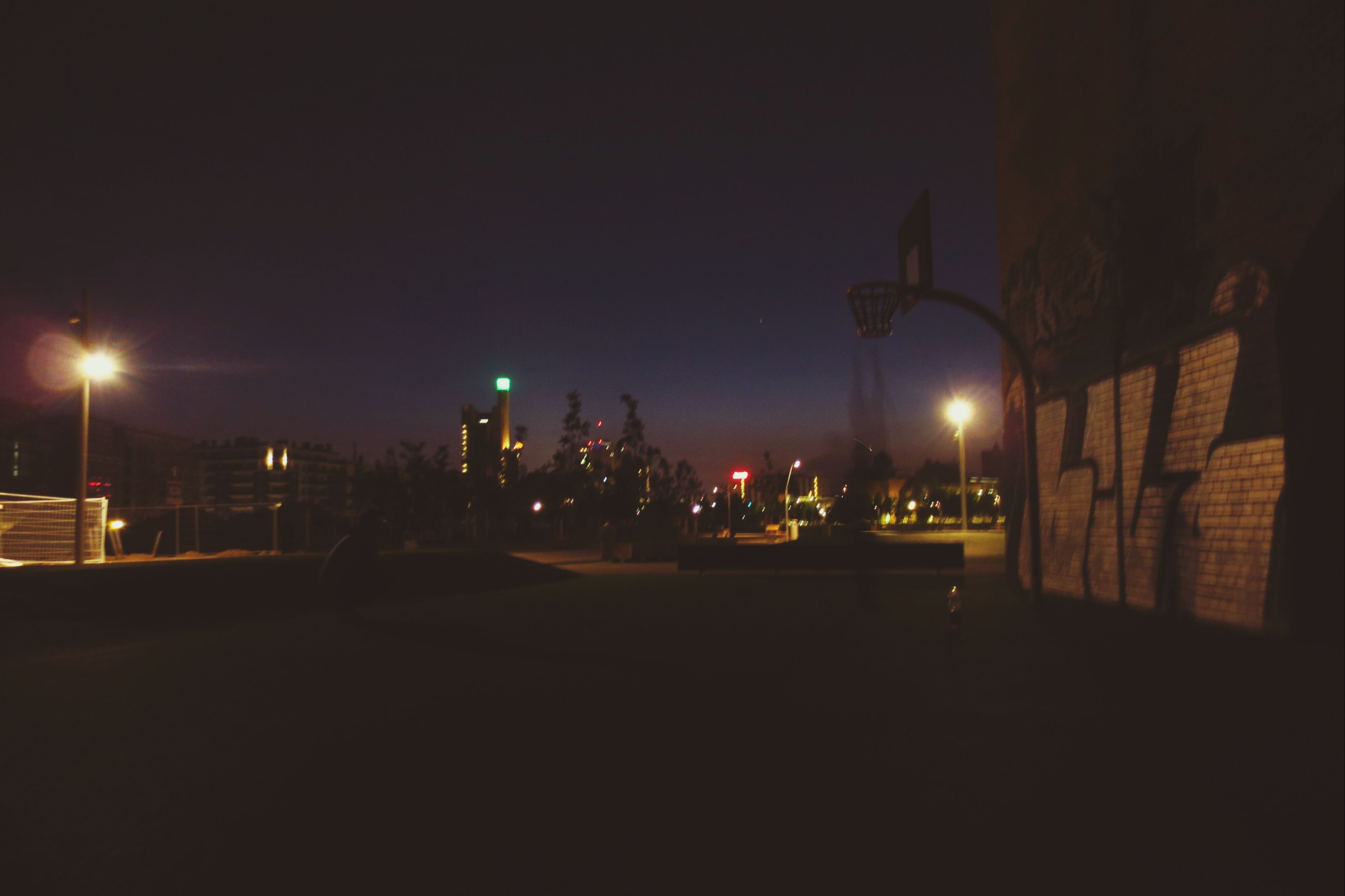 illuminated, night, street light, lighting equipment, building exterior, street, built structure, architecture, clear sky, transportation, city, dark, copy space, road, the way forward, car, outdoors, land vehicle, sky, mode of transport