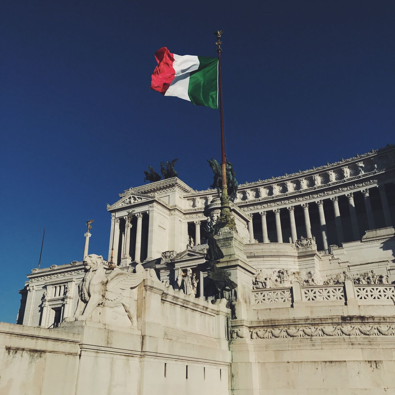flag, patriotism, low angle view, architecture, built structure, building exterior, statue, clear sky, outdoors, sculpture, day, no people, sky