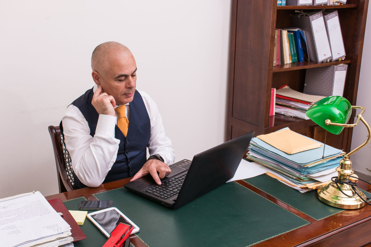 Adult Adults Only Business Business Finance And Industry Businessman Businesswear Day Desk Document Hair Loss Indoors  Looking Down Men Office One Man Only One Person Only Men Paperwork People Shaved Head Sitting Technology Using Laptop Wireless Technology Working
