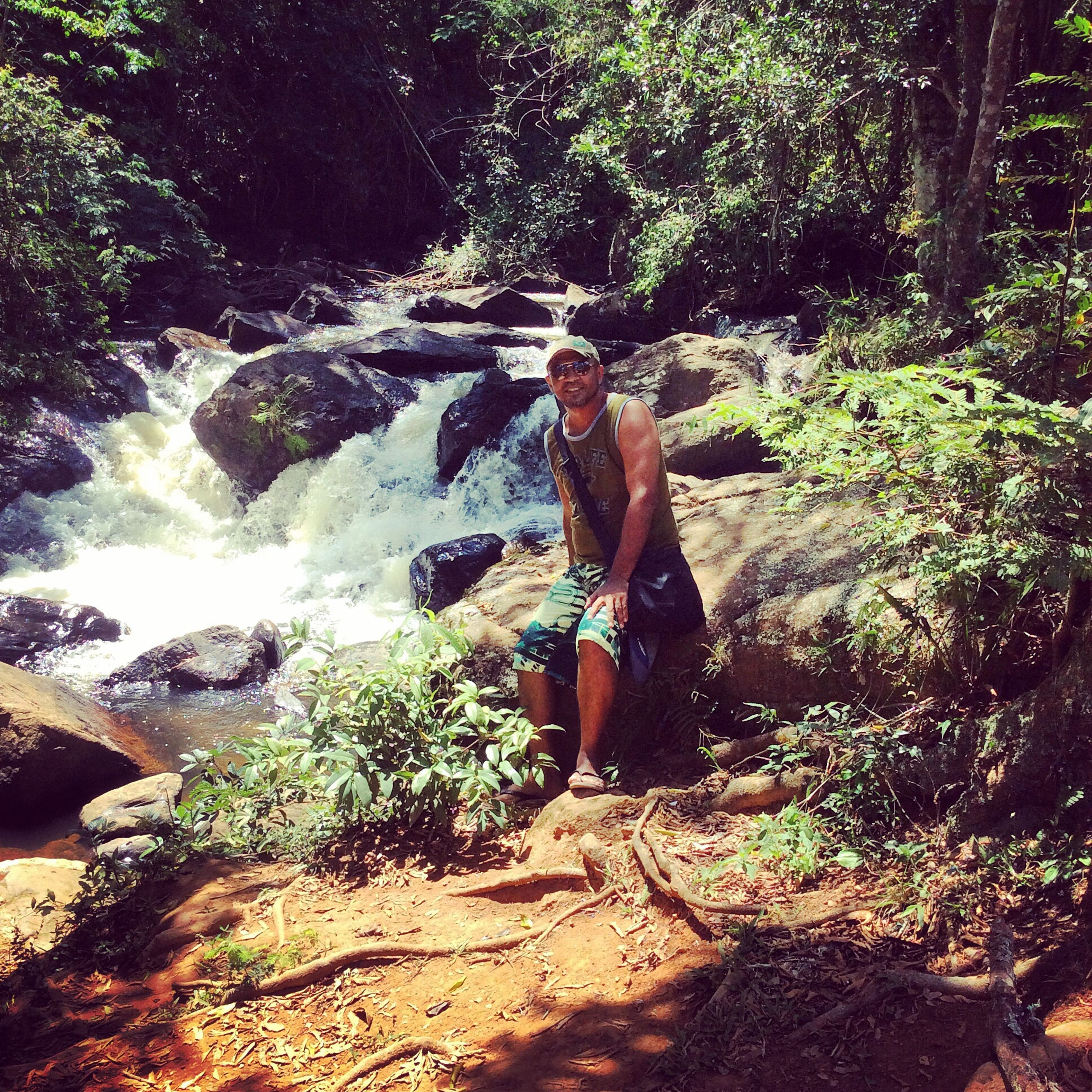 lifestyles, leisure activity, water, full length, rock - object, tree, vacations, forest, men, nature, adventure, motion, young adult, waterfall, enjoyment, beauty in nature, casual clothing, day