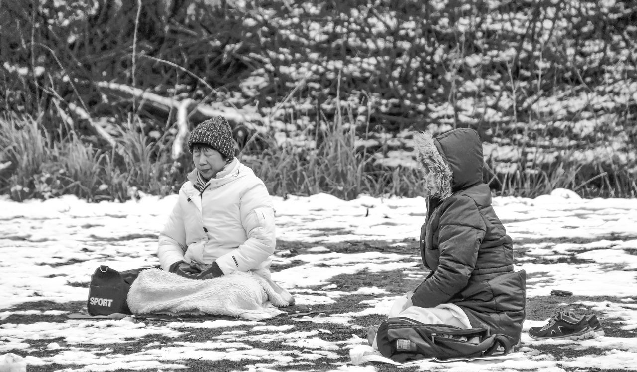 Adult Childhood Cold Temperature Day Flat Cap Focus On Foreground Friendship Full Length Meditation Nature Outdoors People Sitting Snow Togetherness Two People Warm Clothing Winter