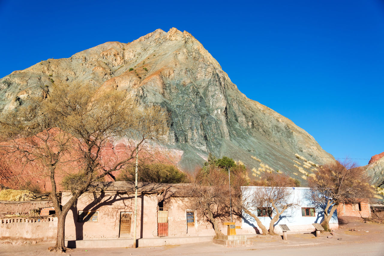 Green, orange, and red hill towering over the plaza of Monte, a small rustic town near Tupiza, Bolivia Andean Andes Beauty Bolivia Canyon Color Colorful Country Countryside Desert Destination Formation Full Hills House Landscape Mountains Nature Plaza Rocks South America Travel TUPIZA Valley Village