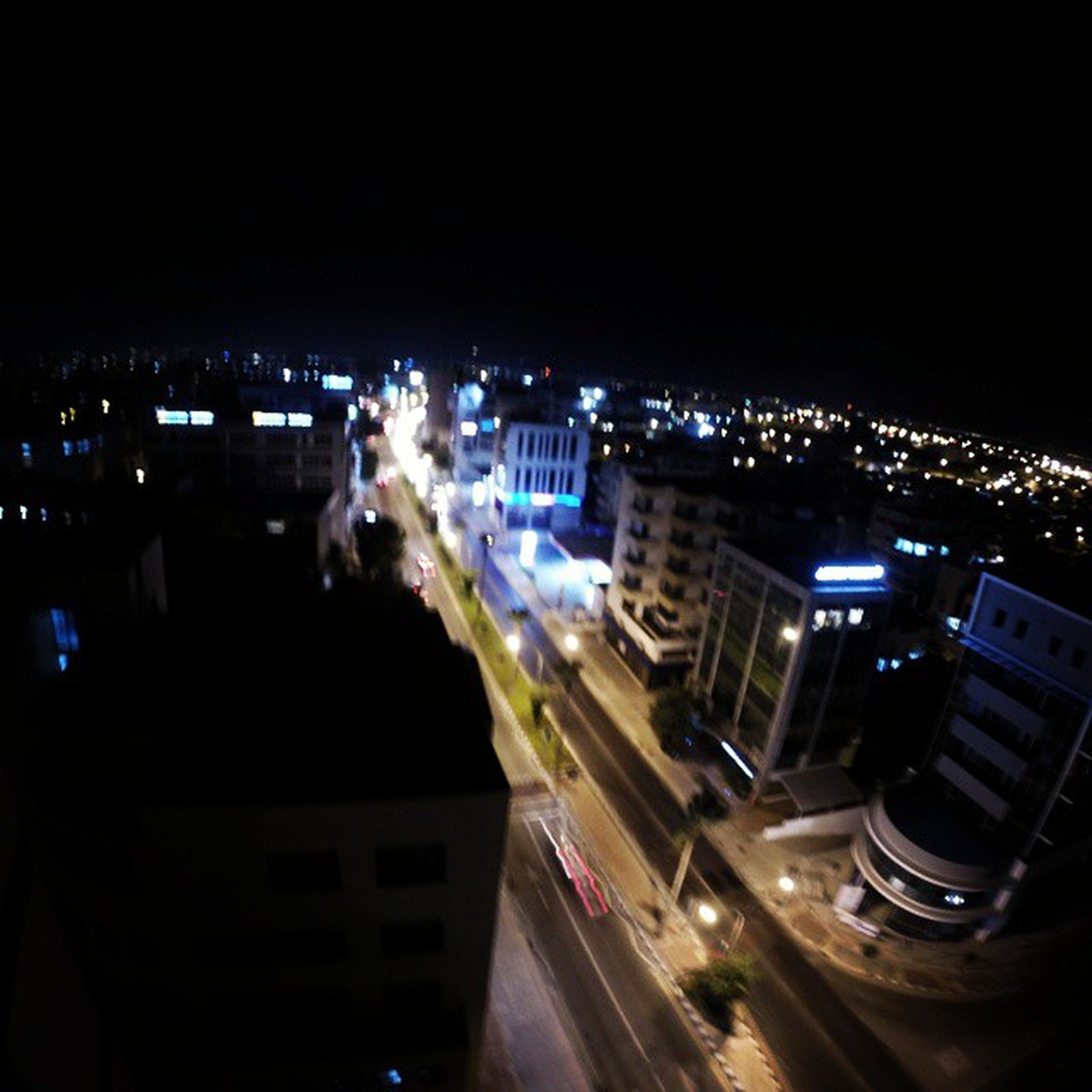 night, illuminated, building exterior, city, architecture, built structure, high angle view, street, transportation, car, cityscape, road, city life, land vehicle, city street, traffic, copy space, dark, clear sky, mode of transport