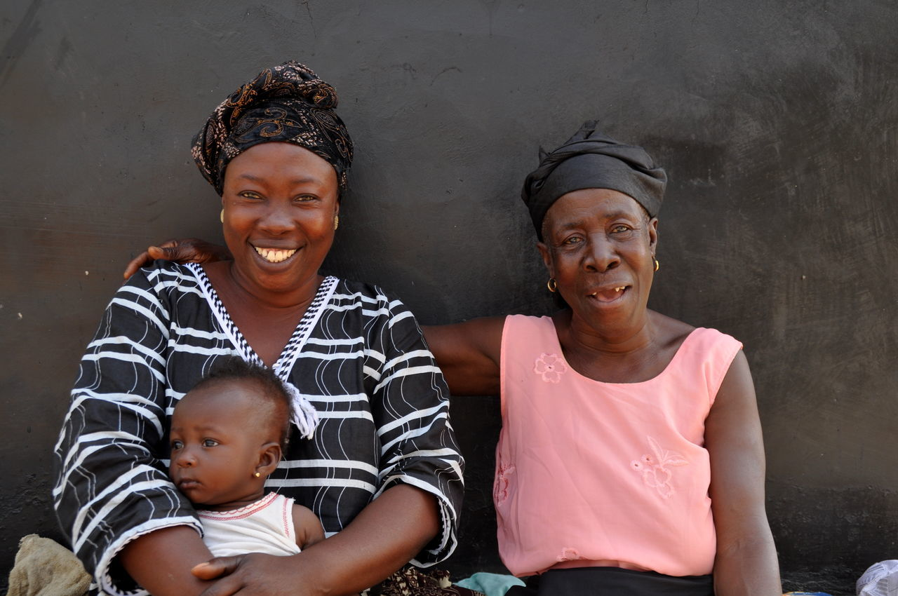 Three Generations Africa Baby Bonding Casual Clothing Childhood Family Family Time Front View Generations Ghana Grandmother Happiness Laughing Looking At Camera Love Mother Outdoors Portrait Real People Sitting Smiling Togetherness Young Adult Young Women Woman