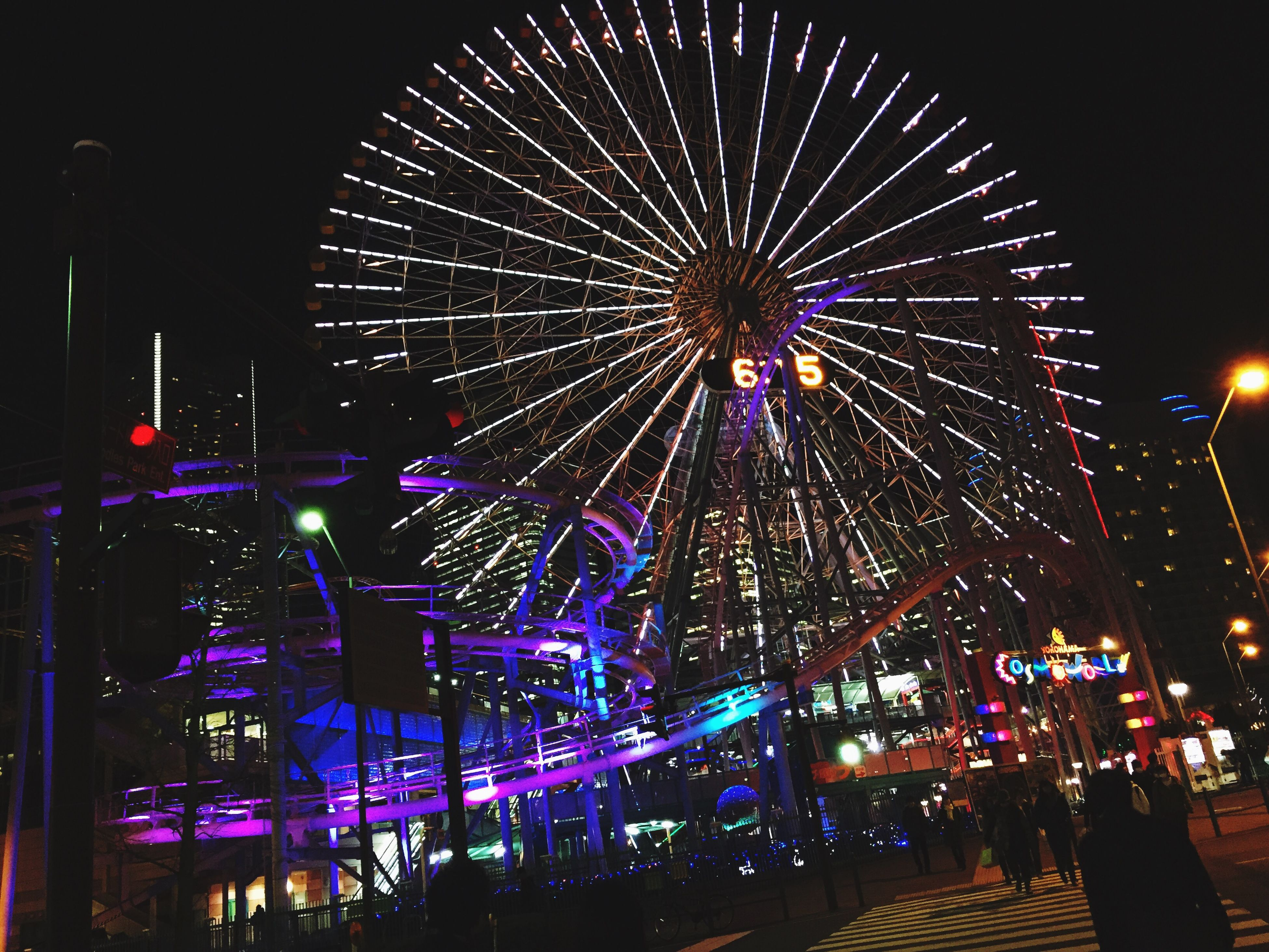 illuminated, night, arts culture and entertainment, amusement park, amusement park ride, ferris wheel, built structure, architecture, building exterior, sky, city, motion, low angle view, celebration, long exposure, leisure activity, firework display, incidental people, lighting equipment, glowing