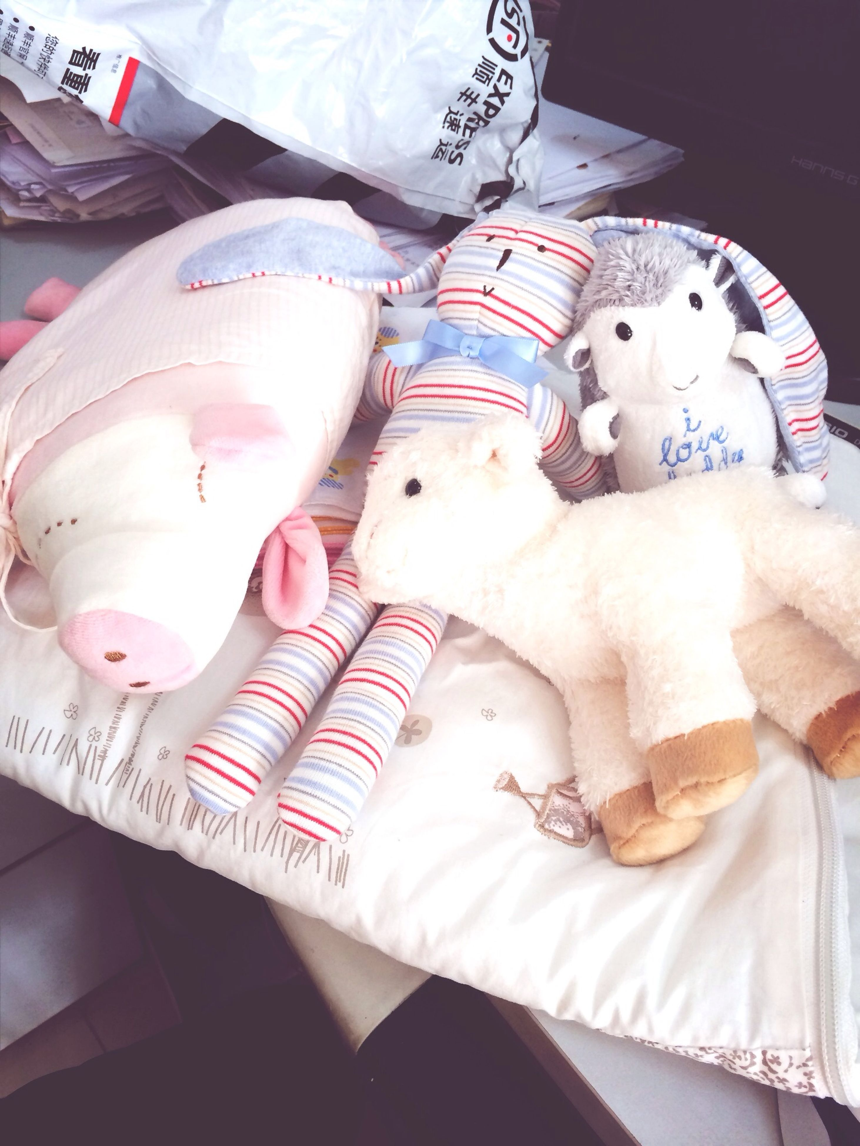 indoors, bed, relaxation, stuffed toy, high angle view, pillow, animal representation, toy, lying down, animal themes, blanket, resting, home interior, domestic animals, white color, bedroom, sitting, pets
