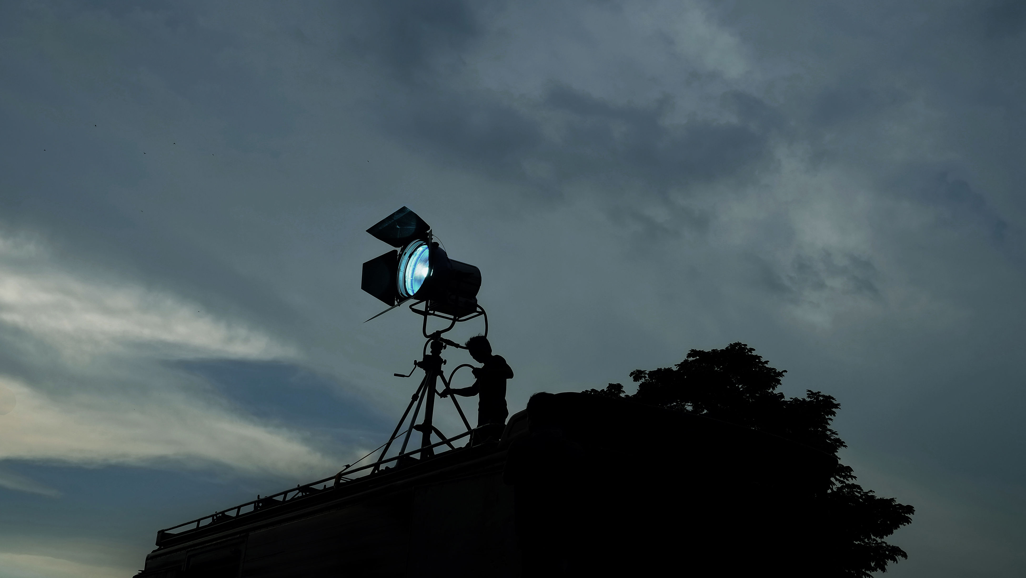 Low Angle View Of Silhouette Man Standing With Illuminated Lighting Equipment Against Cloudy Sky At Dusk