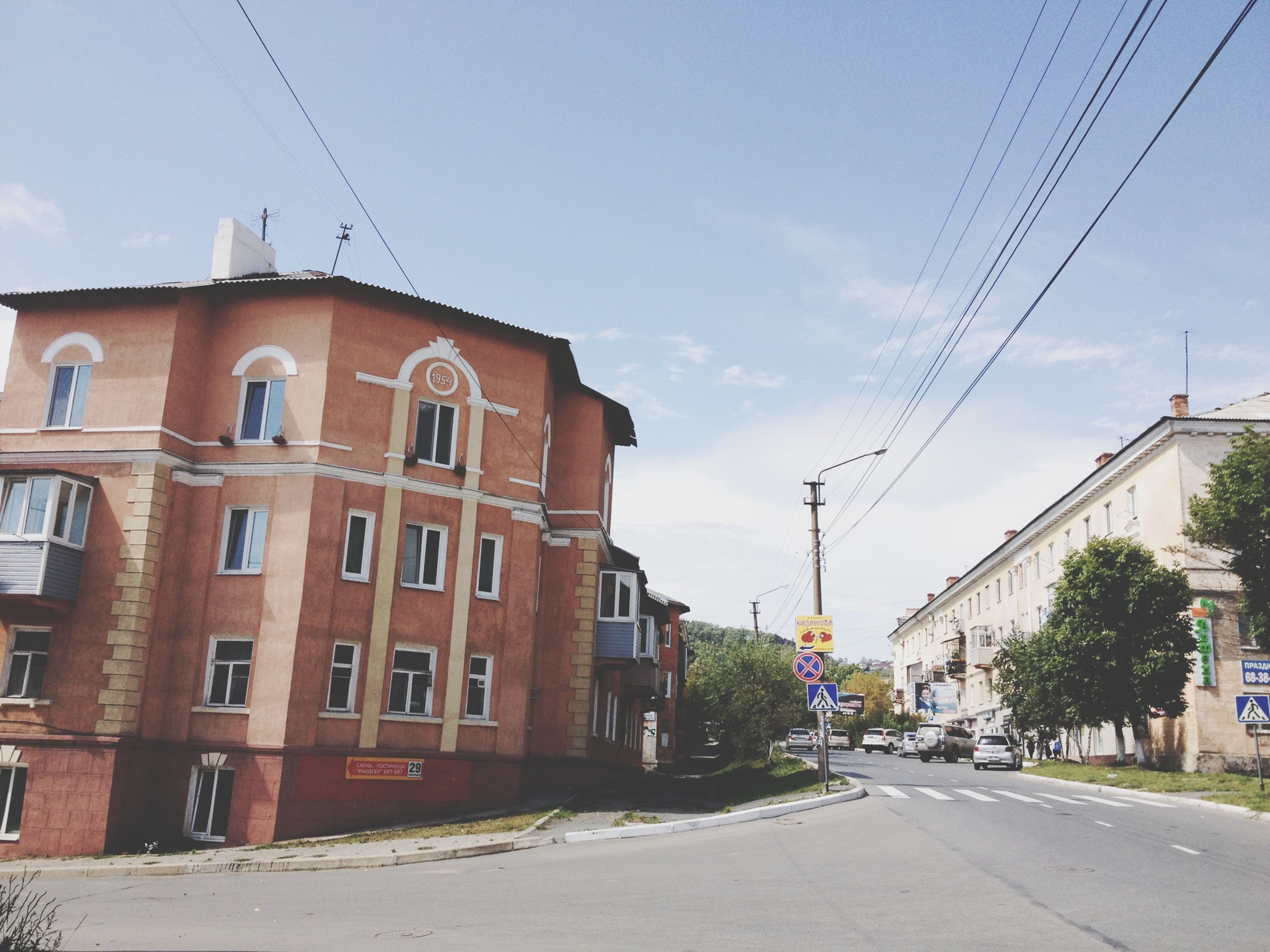 building exterior, power line, architecture, built structure, electricity pylon, cable, street, sky, road, electricity, transportation, power supply, the way forward, house, power cable, residential structure, residential building, city, diminishing perspective, outdoors