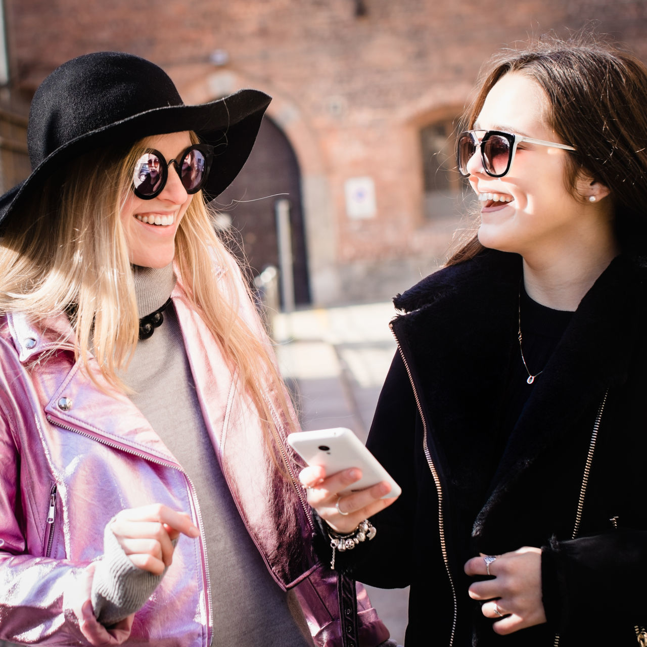 Adult Adults Only Blond Hair Cheerful Communication Day Fashion Friendship Internet Mobile Phone Only Women Outdoors People Portable Information Device Smart Phone Smiling Sunglasses Two People Wireless Technology Women Young Adult Young Women