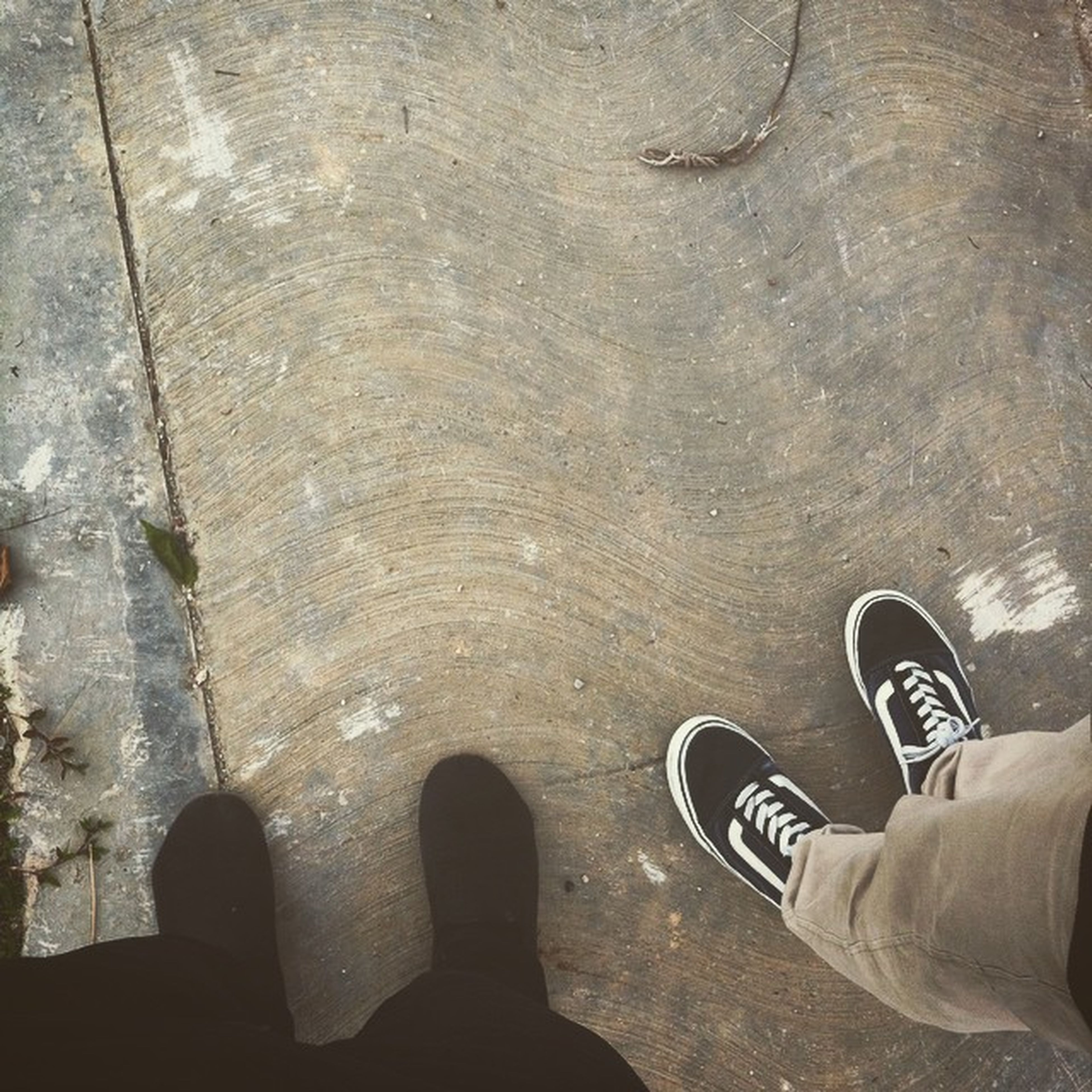 low section, shoe, person, personal perspective, standing, high angle view, lifestyles, men, footwear, human foot, directly above, unrecognizable person, street, leisure activity, part of, textured, day