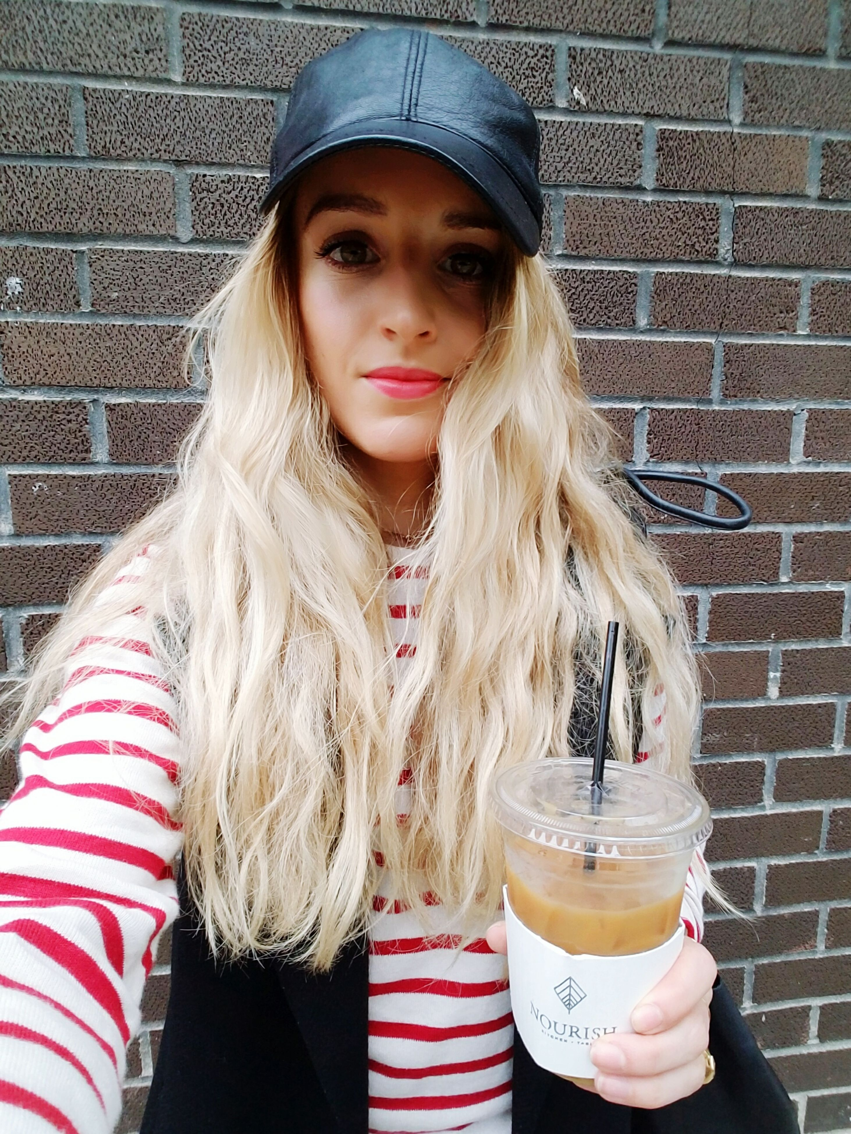 portrait, looking at camera, real people, front view, drinking, brick wall, drink, lifestyles, one person, long hair, young women, young adult, drinking straw, beautiful woman, drinking glass, leisure activity, blond hair, outdoors, standing, day, adult, people