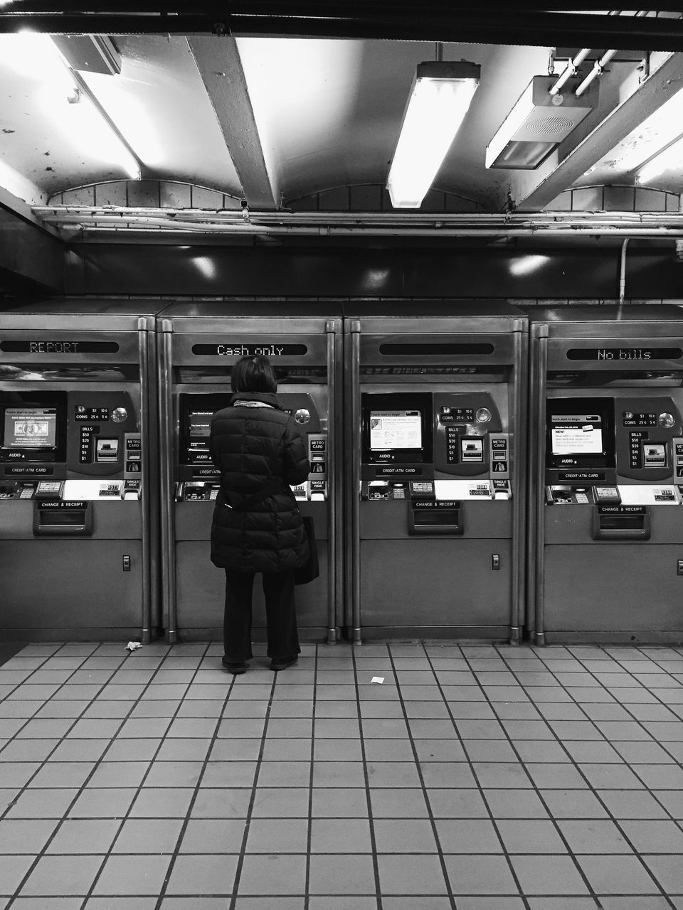 Rear View Of Person Standing Against Automated Teller Machine At Airport