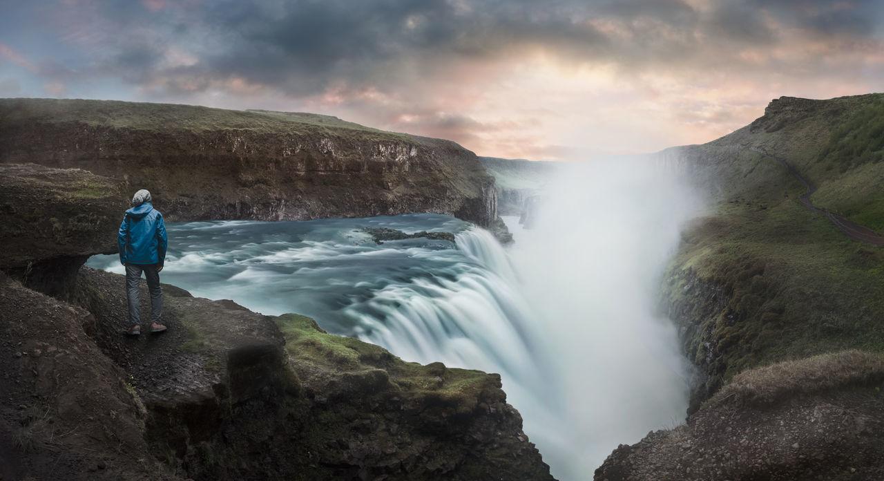 Rear View Of Man Walking At Gullfoss Waterfall During Sunset