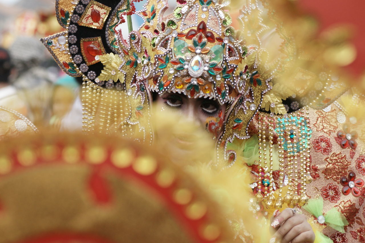 gold colored, selective focus, close-up, venetian mask, multi colored, no people, indoors, day