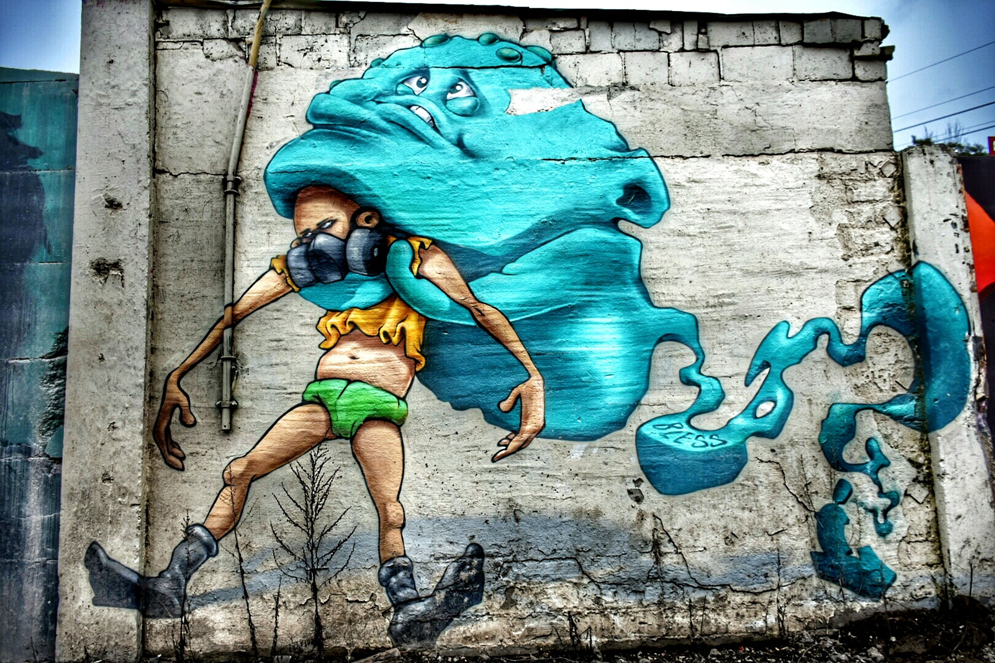 full length, architecture, built structure, building exterior, wall - building feature, casual clothing, blue, lifestyles, person, standing, leisure activity, front view, graffiti, brick wall, young adult, wall, portrait, looking at camera
