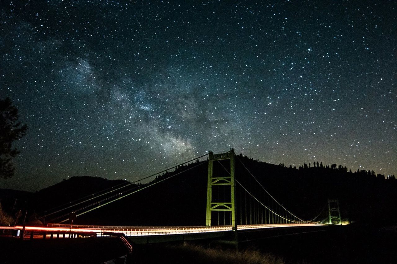 Low Angle View Of Illuminated Bridge By Mountain Against Starry Sky