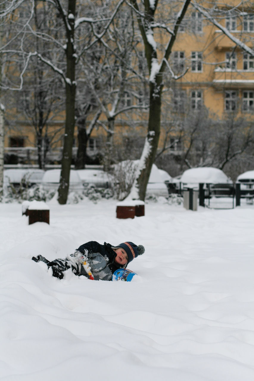 Boy Playing On Snow Covered Field
