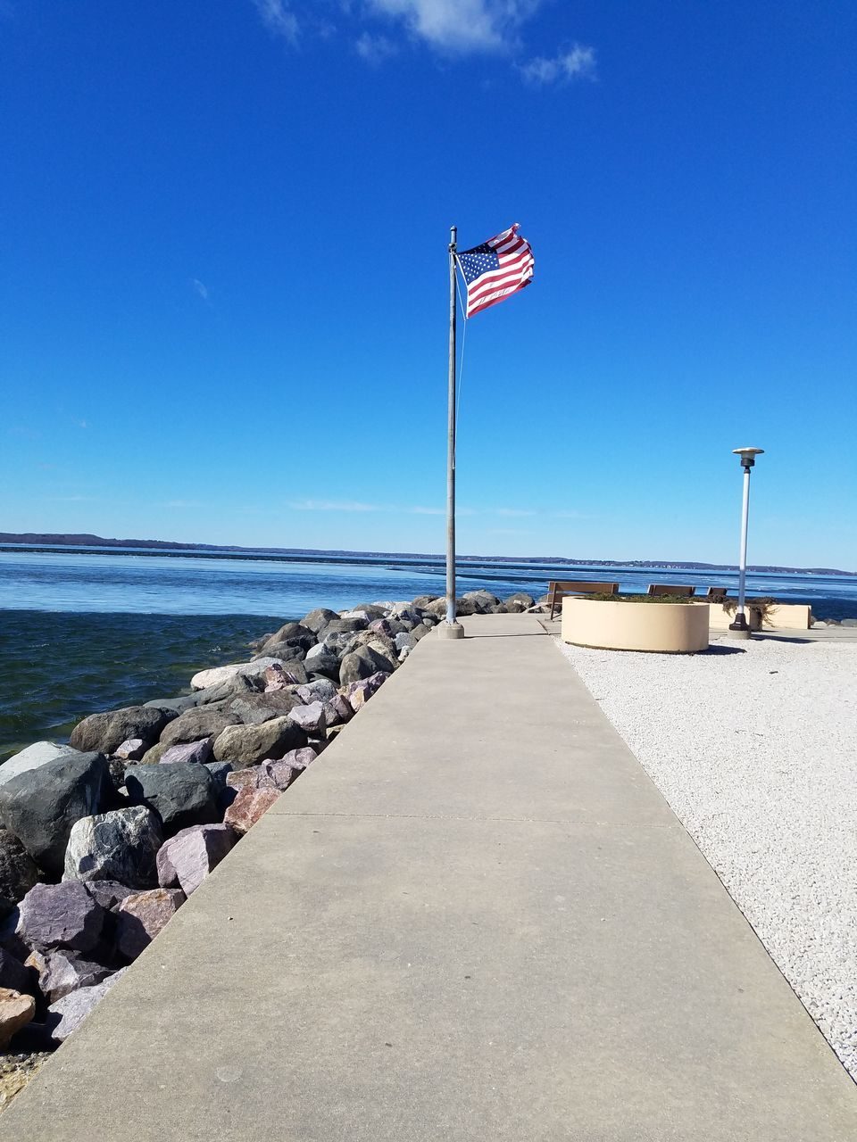 flag, patriotism, sea, water, flag pole, striped, day, blue, nature, sky, no people, horizon over water, stars and stripes, outdoors, clear sky, scenics, tranquility, beauty in nature