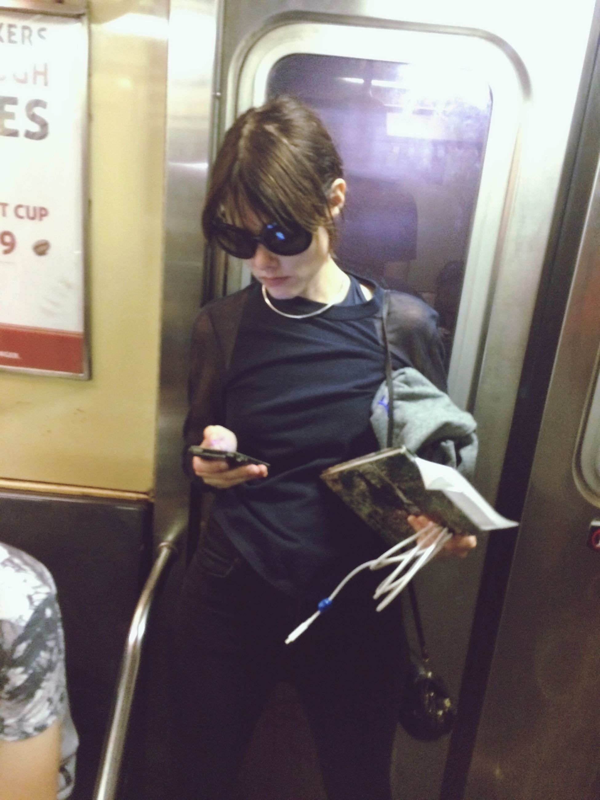 indoors, transportation, lifestyles, vehicle interior, mode of transport, public transportation, casual clothing, travel, technology, young adult, window, leisure activity, train - vehicle, three quarter length, person, holding, sitting, glass - material