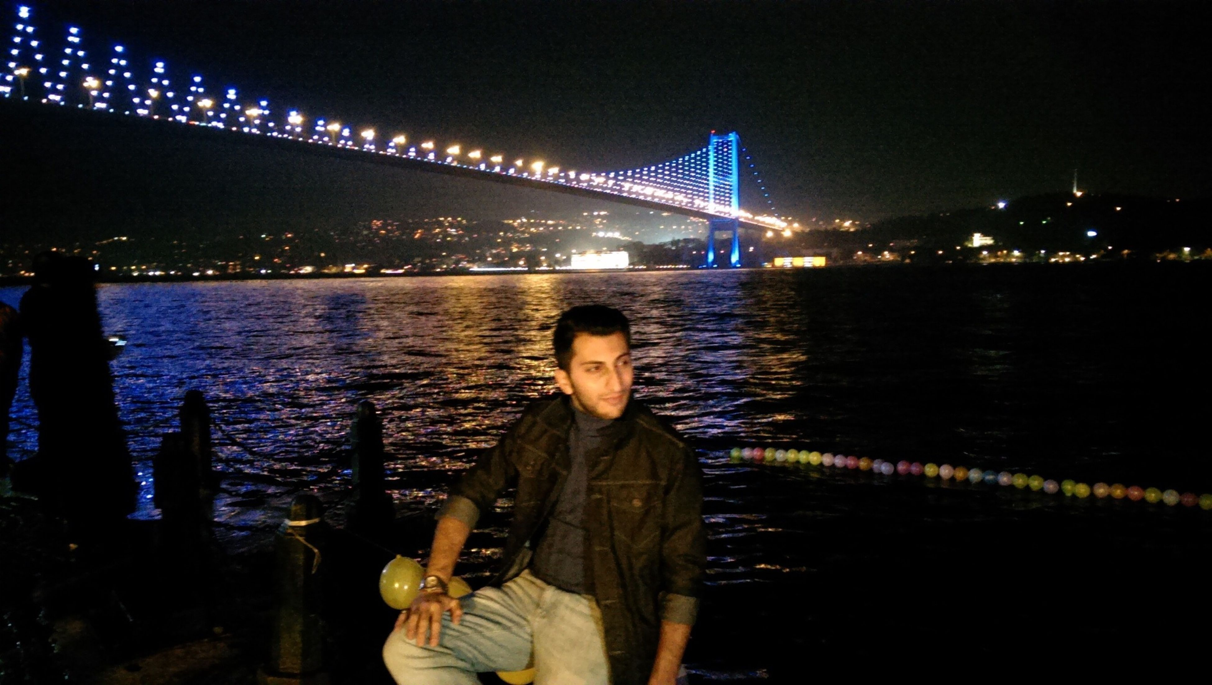 water, lifestyles, night, illuminated, architecture, built structure, standing, river, leisure activity, connection, young adult, casual clothing, bridge - man made structure, person, full length, young women, rear view, city