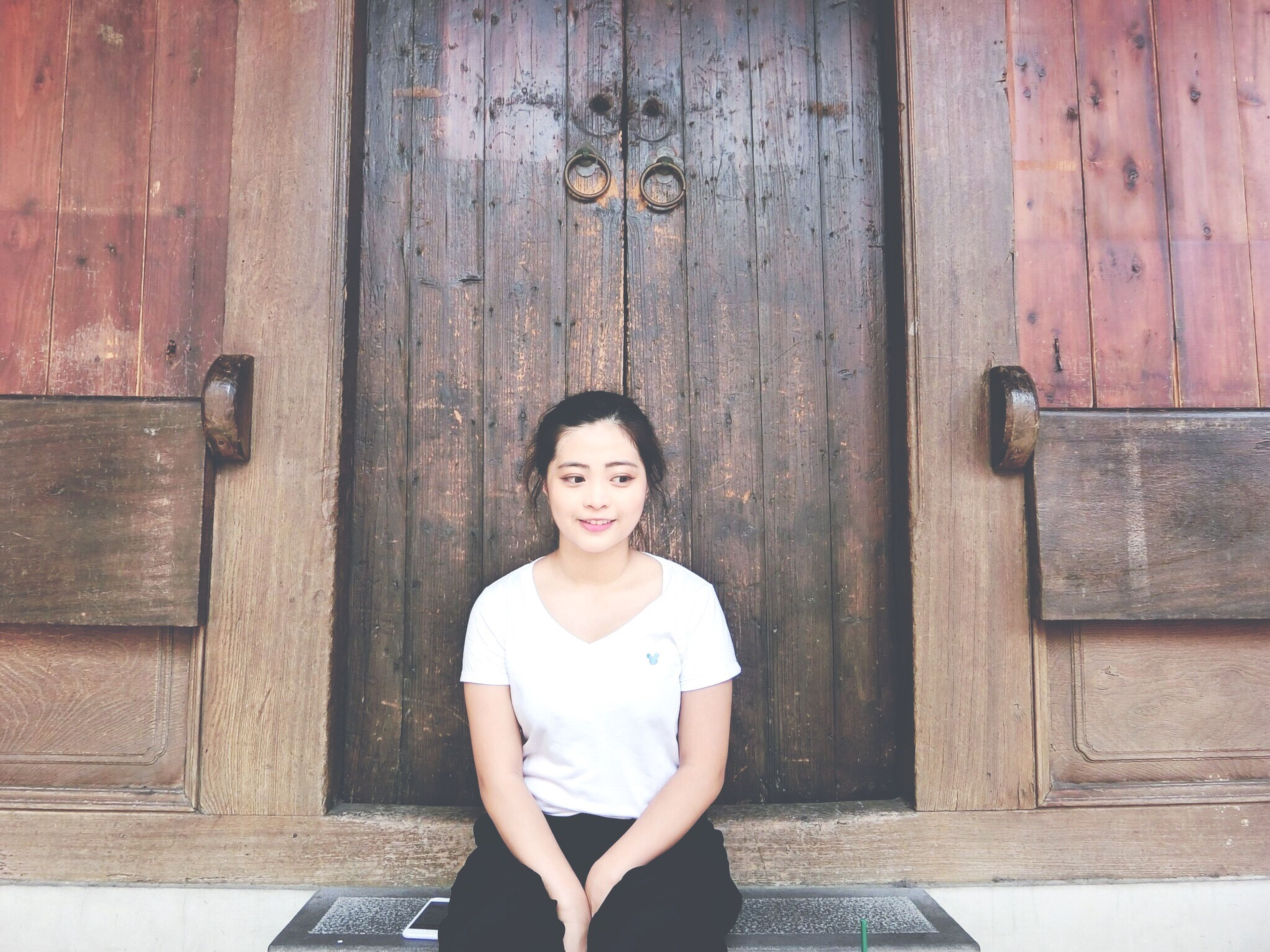 wood - material, wooden, front view, standing, person, looking at camera, lifestyles, door, casual clothing, portrait, smiling, built structure, wood, childhood, leisure activity, building exterior, architecture, elementary age