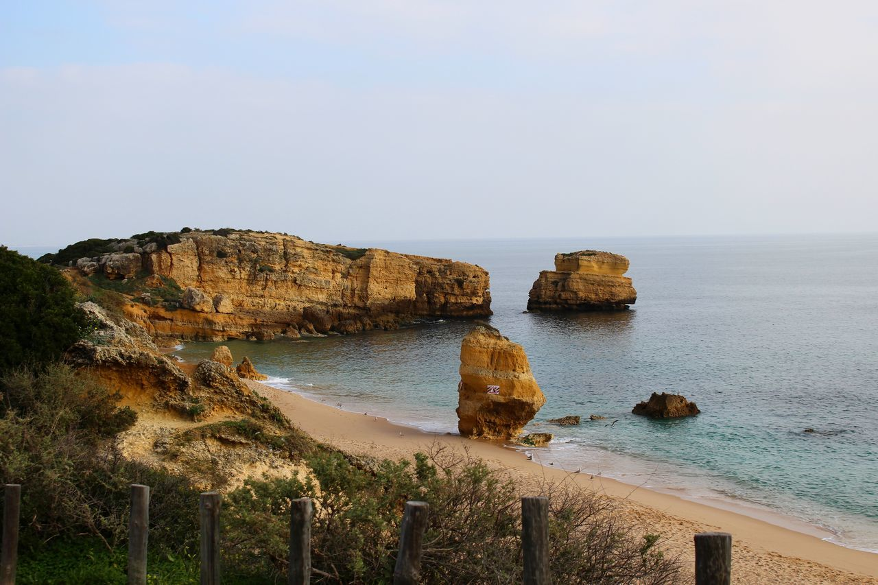 Algarve Beach Beauty In Nature Cliff Cloudy Coastline Day Exceptional Photographs Fence Geology Horizon Over Water Nature No People Ocean Outdoors Plants Portugal Rock Rocks Rocky Sand Travel Destinations Tree View From Above Water