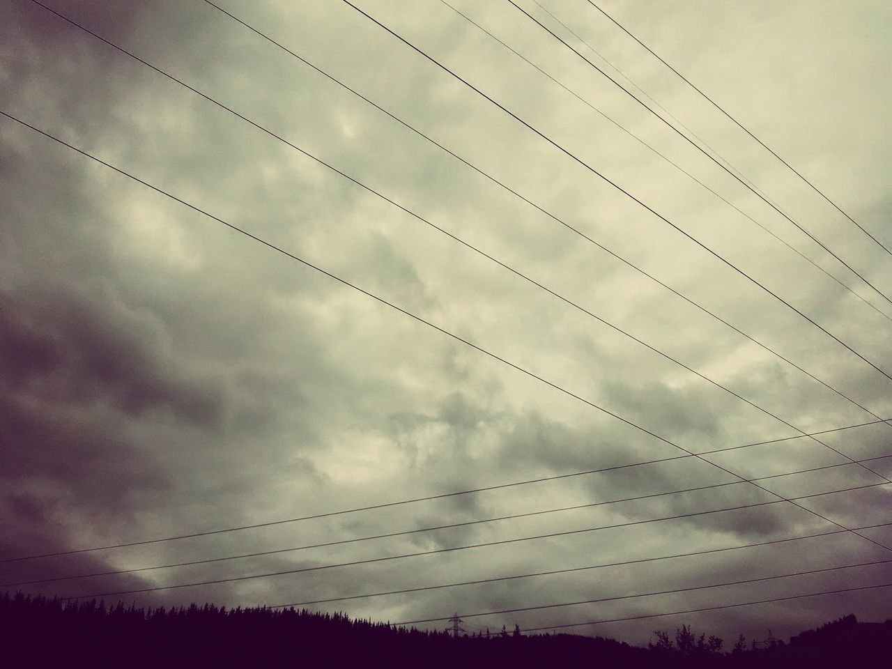 Low Angle View Of Cables Against Clouds
