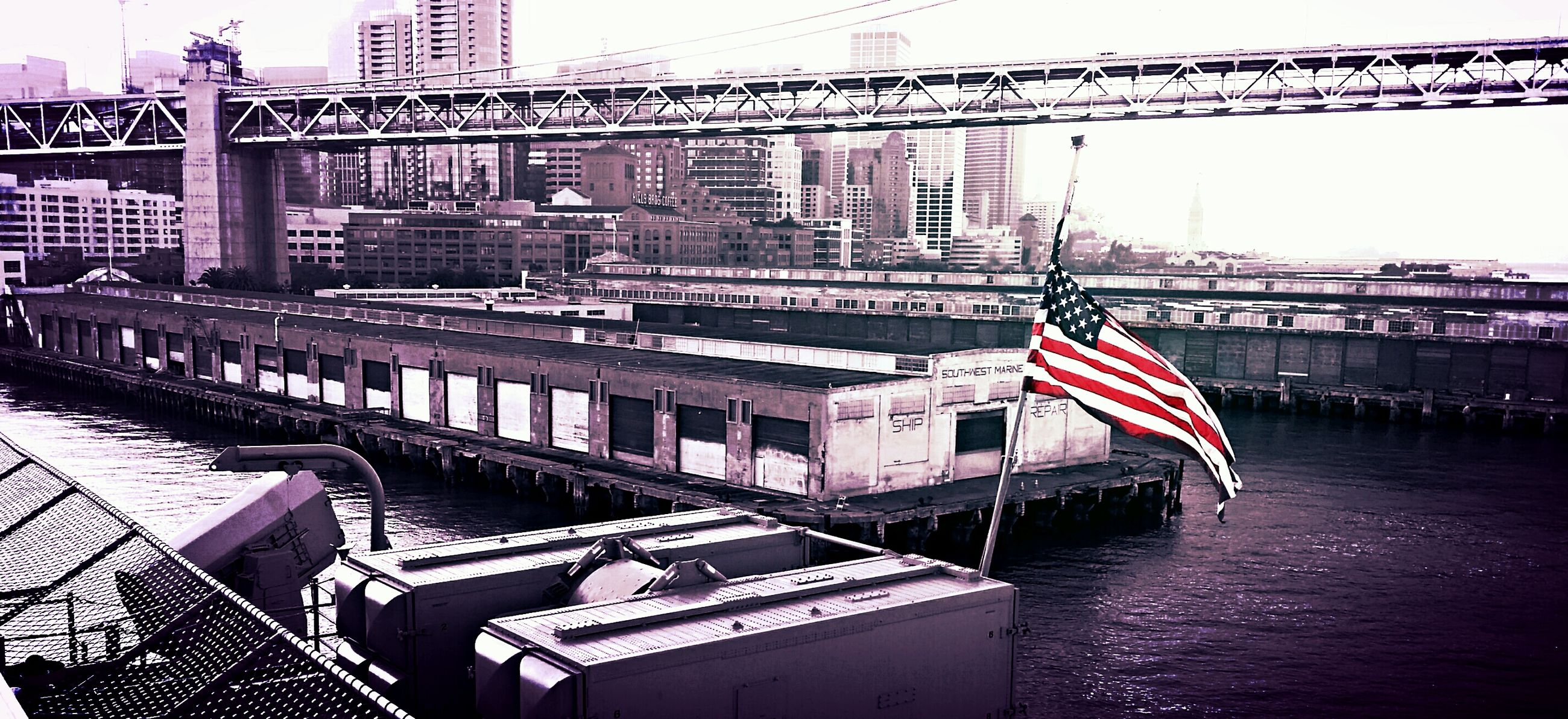 architecture, built structure, building exterior, city, flag, clear sky, transportation, american flag, river, water, connection, day, red, nautical vessel, patriotism, outdoors, waterfront, national flag, no people, bridge - man made structure