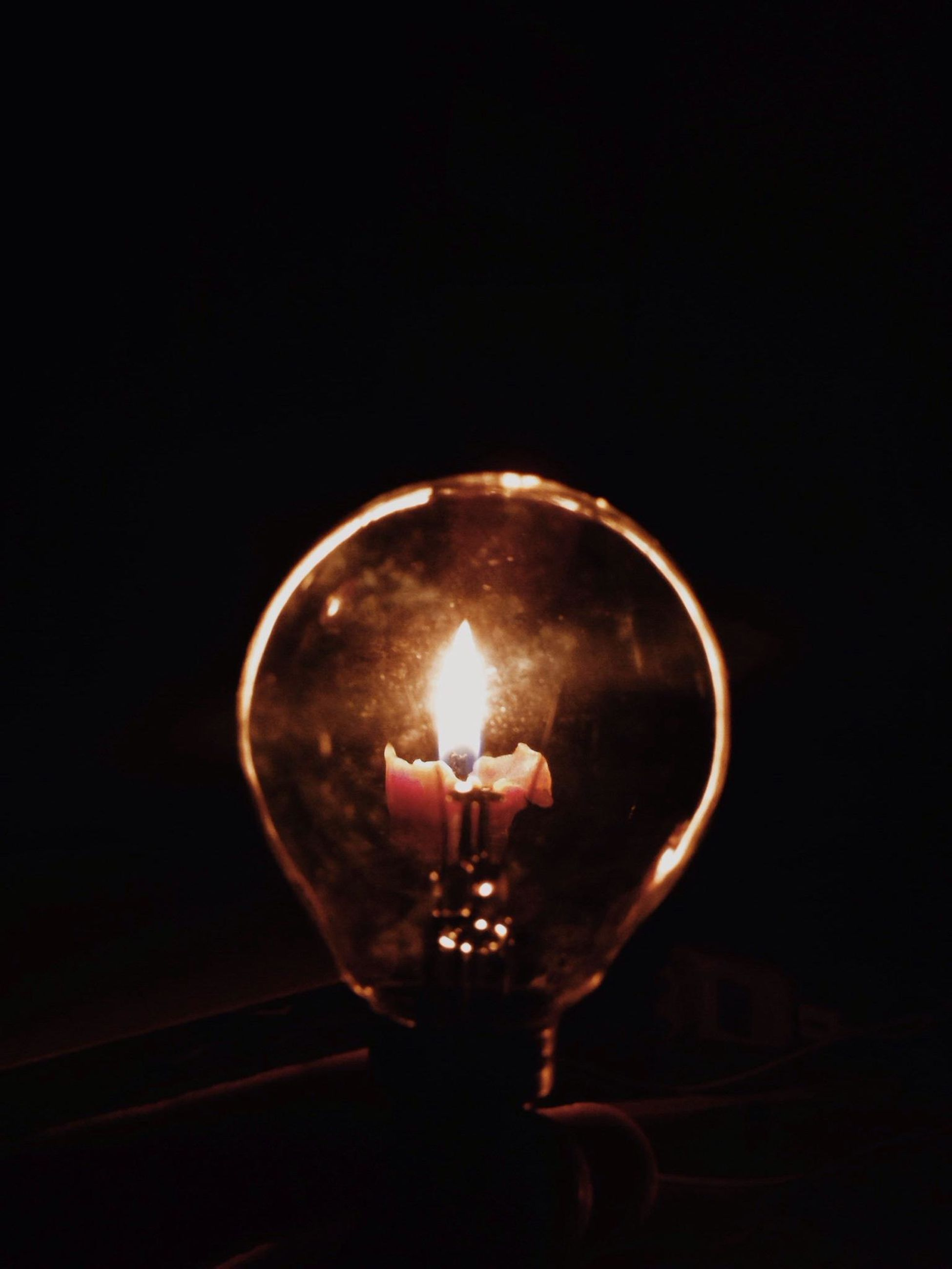 illuminated, indoors, lighting equipment, light bulb, glowing, electricity, lit, burning, close-up, glass - material, flame, electric light, dark, copy space, transparent, night, fire - natural phenomenon, darkroom, candle, heat - temperature