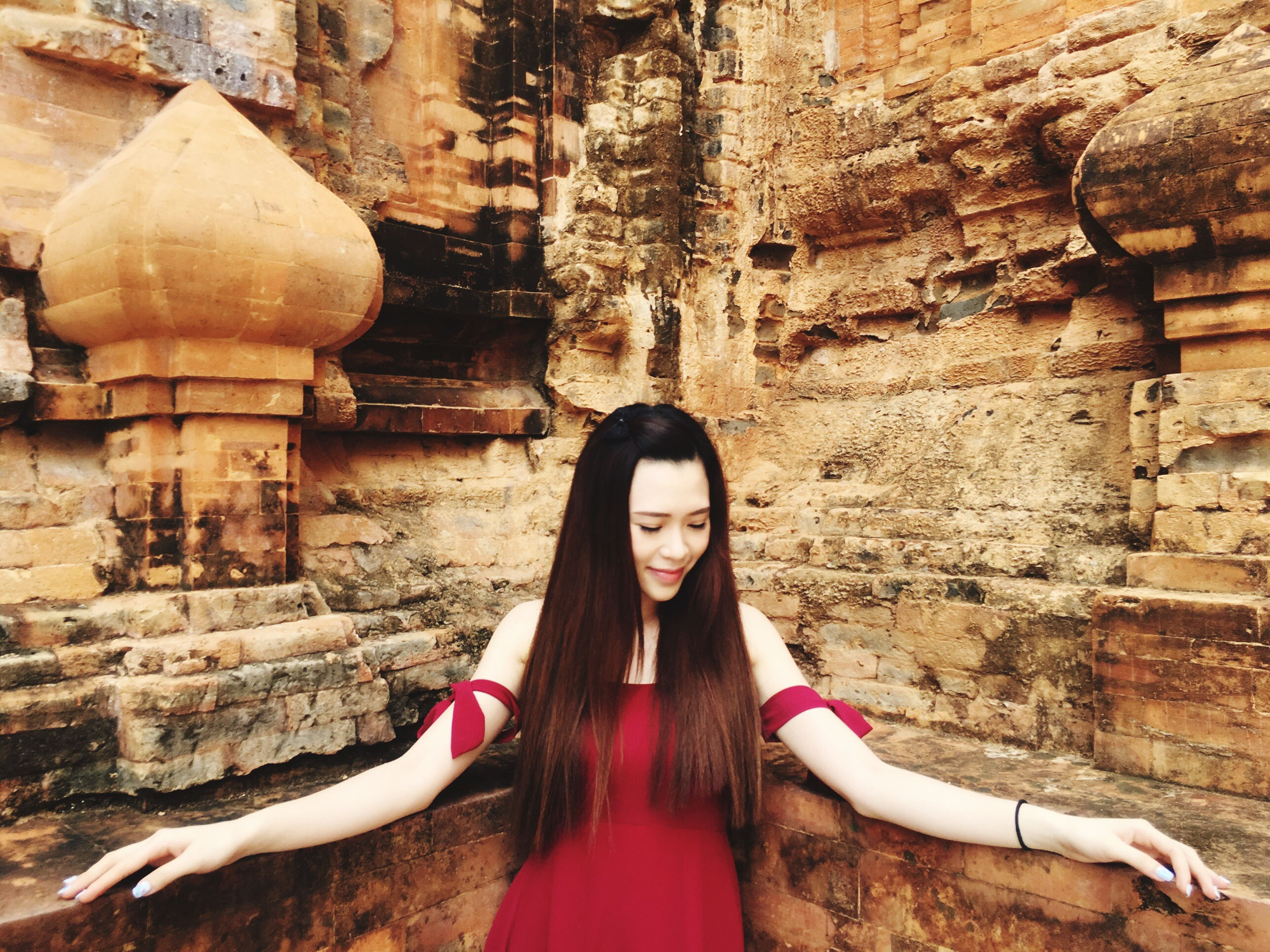young adult, architecture, young women, built structure, wall - building feature, building exterior, long hair, person, casual clothing, history, beauty, outdoors, red, famous place, ancient