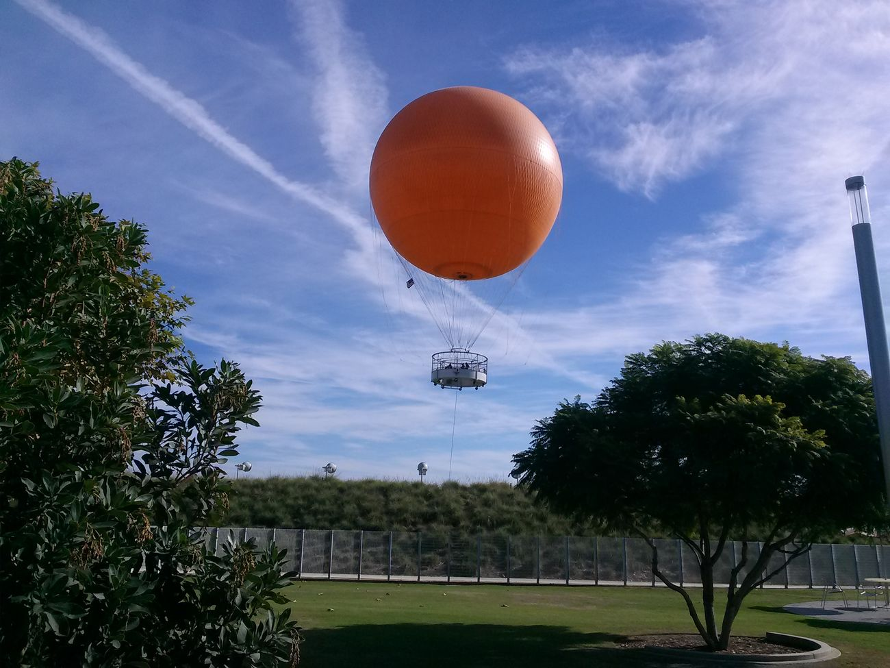 at the Great Park of Orange County, the former grounds for the El Toro Marine Base. in its infancy, the Park is twice the size of Central Park in New York City. the big orange balloon is probably the park's most identifiable feature. for ten dollars you can take a ride up at the rste of 3 feet per second to a height of 400 feet. Hot Air Balloon At The Park Sunday Afternoon Enjoying Life