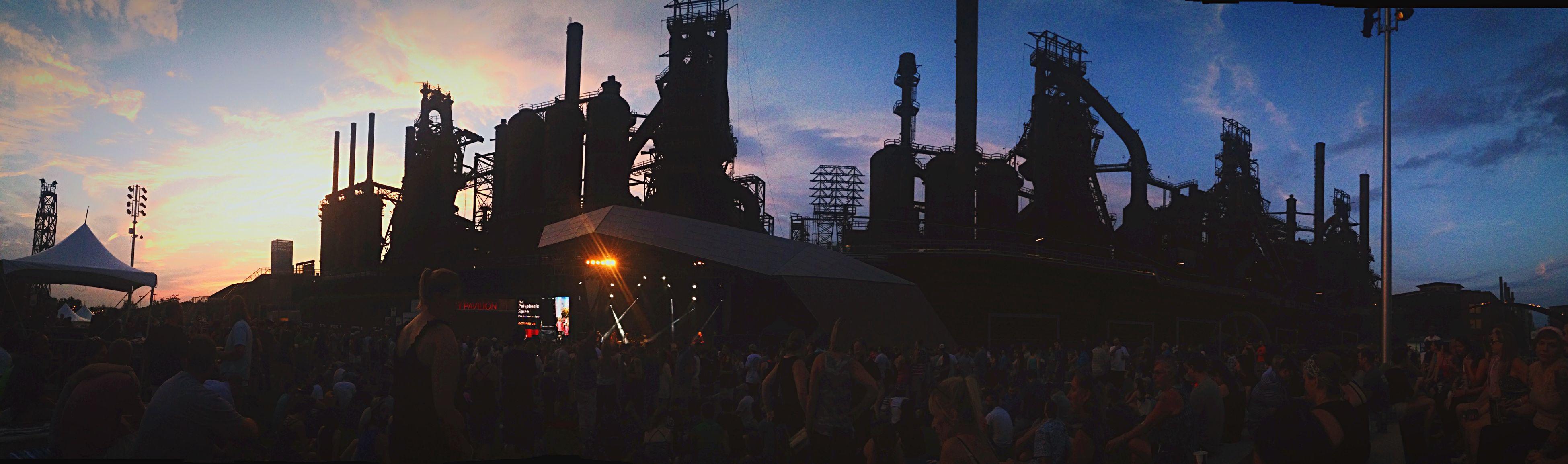 sky, built structure, building exterior, architecture, sunset, silhouette, dusk, illuminated, city, crane - construction machinery, low angle view, outdoors, cloud - sky, large group of people, development, construction site, crane, arts culture and entertainment, city life, cloud