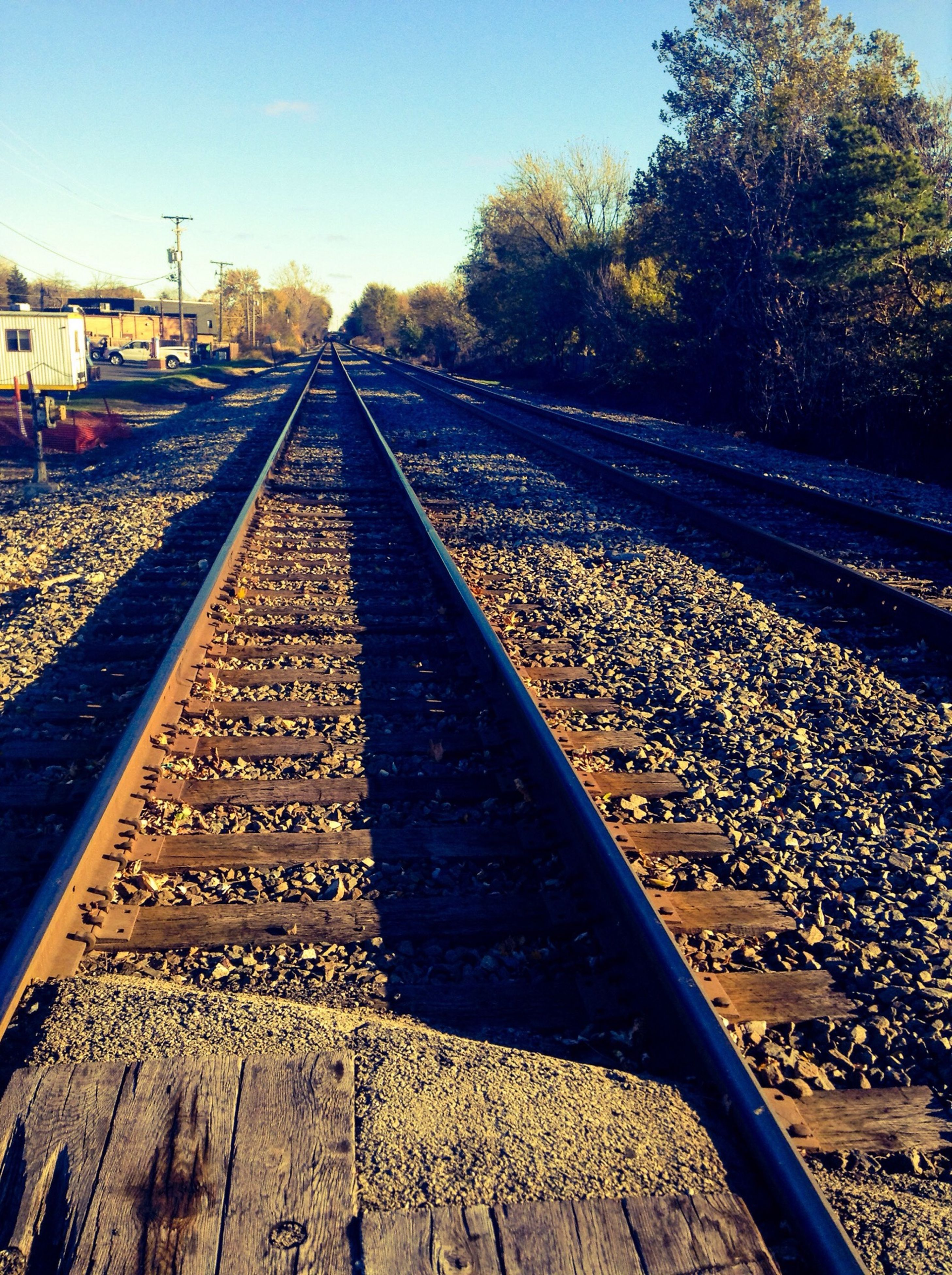 transportation, railroad track, diminishing perspective, the way forward, rail transportation, vanishing point, tree, clear sky, sky, road, road marking, surface level, travel, railway track, day, outdoors, public transportation, no people, stone - object, metal