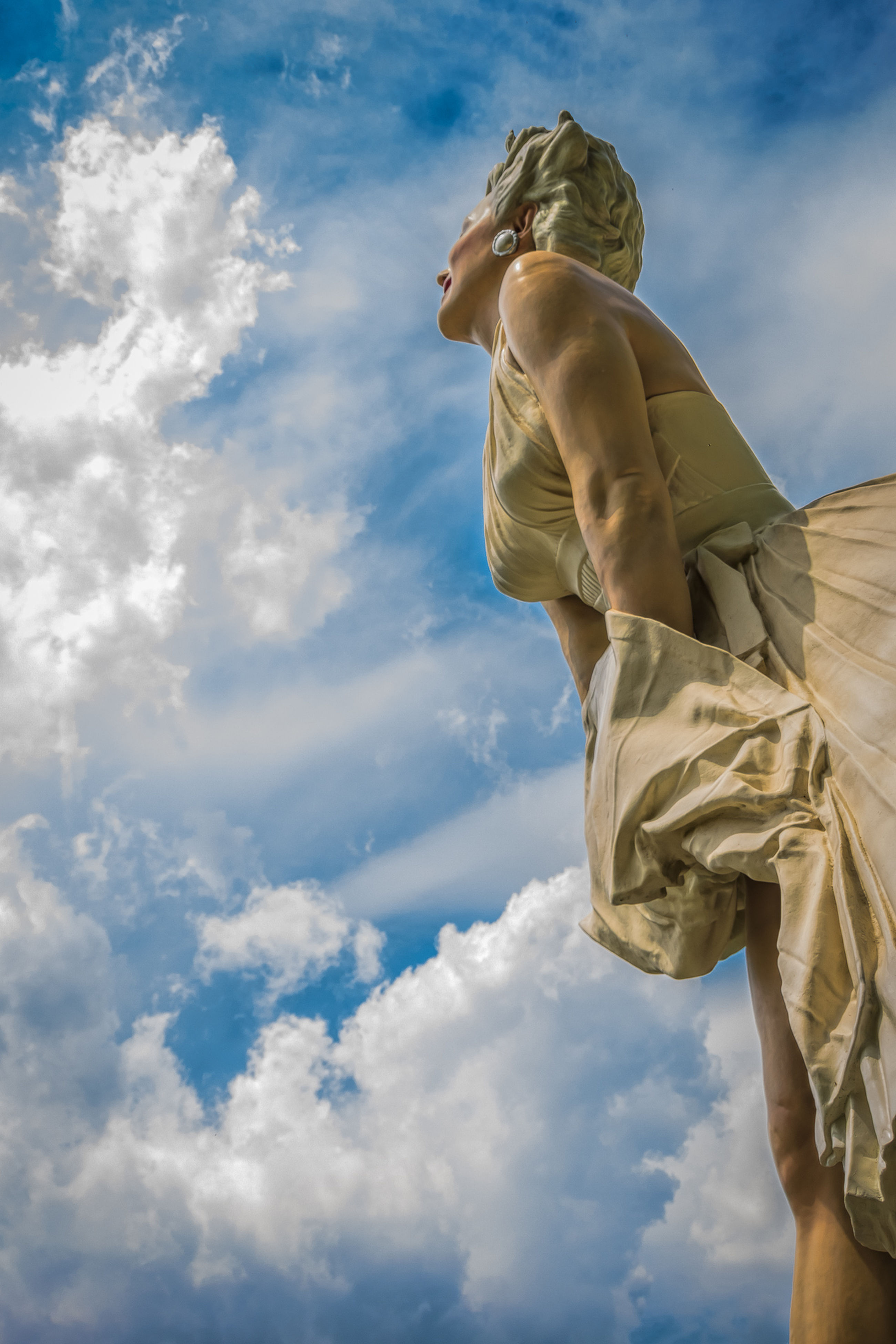 low angle view, sky, statue, sculpture, human representation, cloud - sky, art and craft, cloud, art, creativity, cloudy, day, outdoors, no people, sunlight, blue, nature, part of