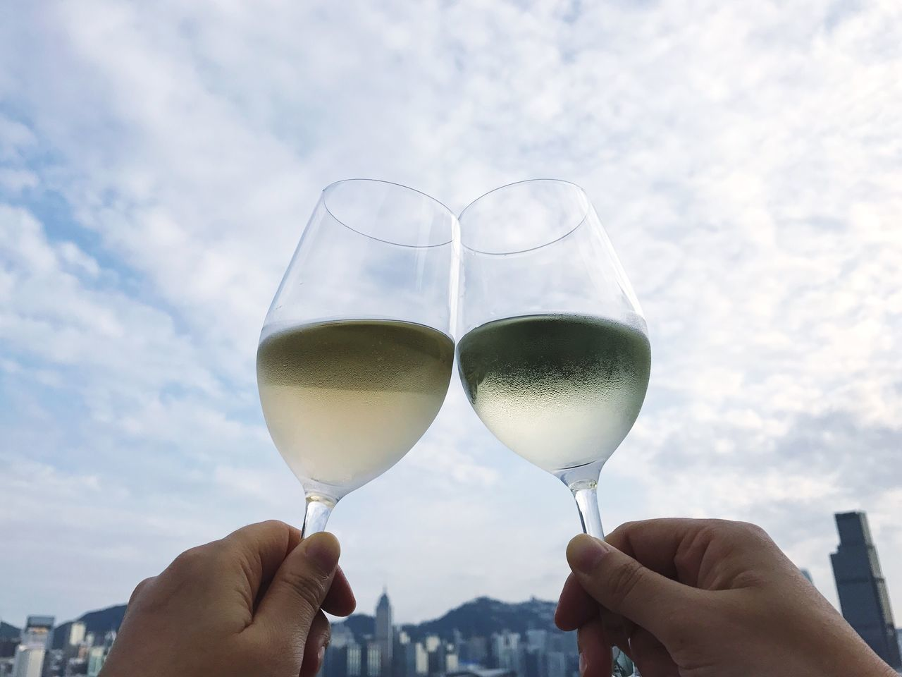 Human Hand Human Body Part Food And Drink Holding Real People Drink Personal Perspective Alcohol Unrecognizable Person Leisure Activity Focus On Foreground Sky One Person Drinking Glass Refreshment Lifestyles Cloud - Sky Outdoors Wineglass Day