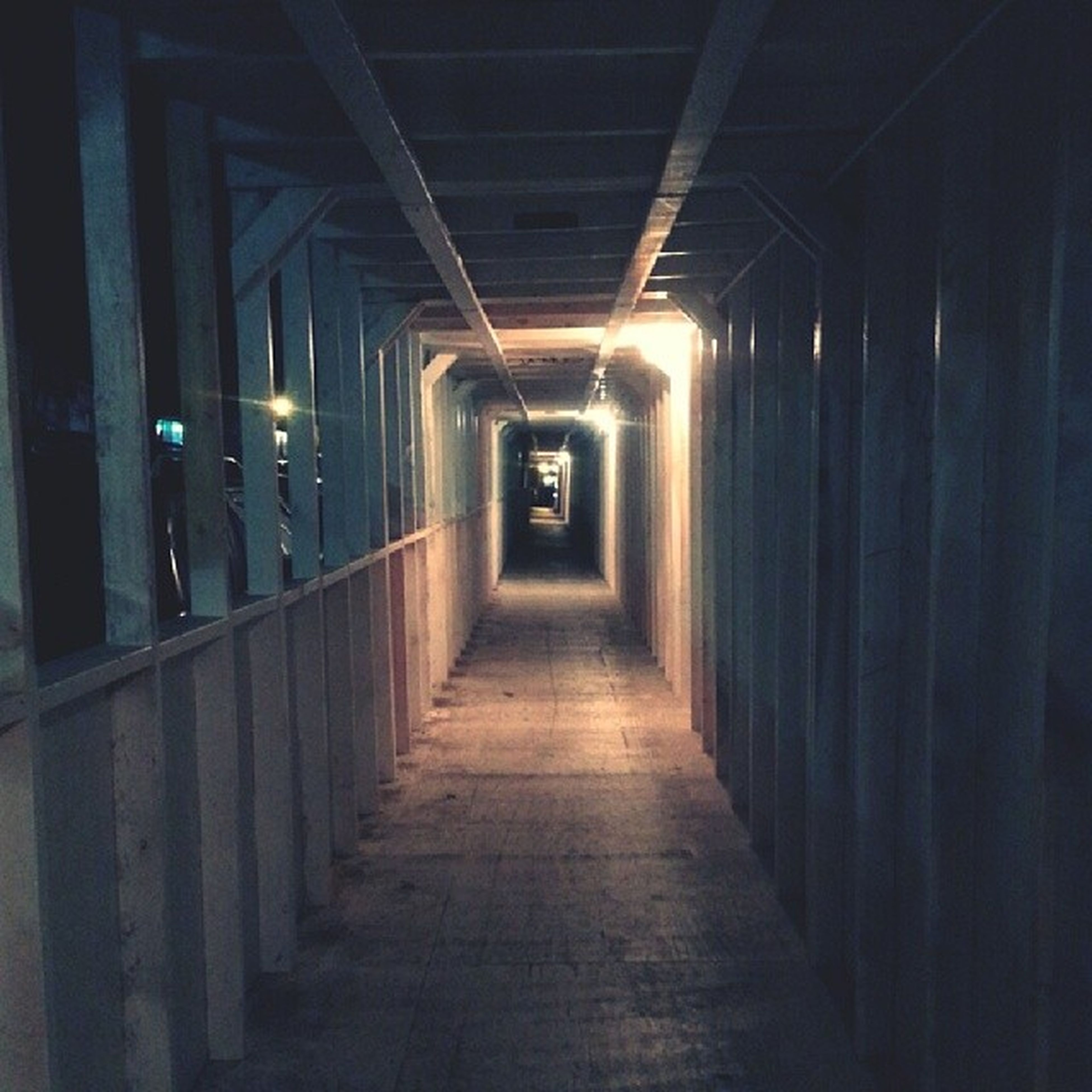 indoors, the way forward, illuminated, corridor, diminishing perspective, architecture, built structure, vanishing point, architectural column, ceiling, lighting equipment, empty, in a row, narrow, night, column, flooring, colonnade, walkway, long
