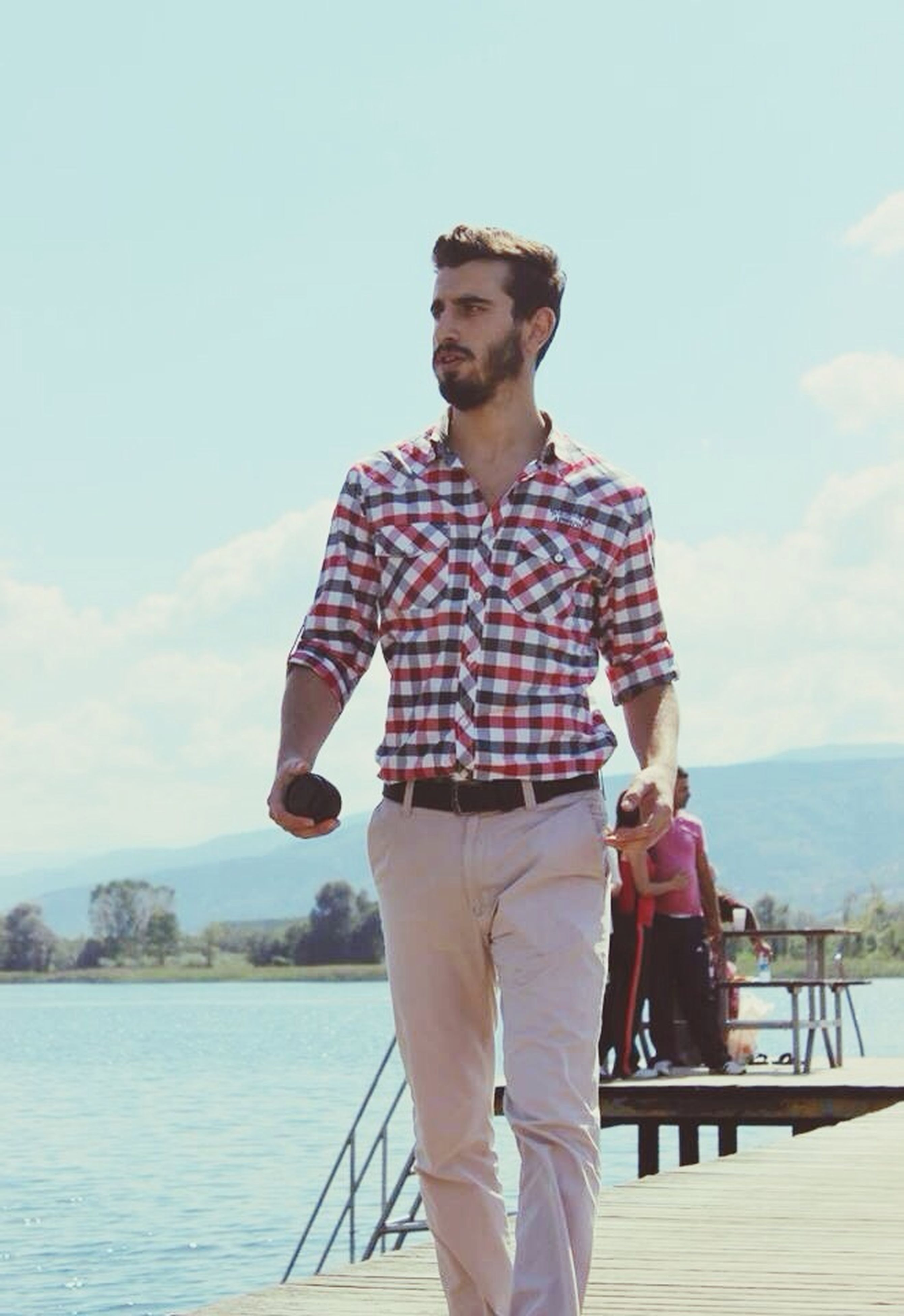 water, lifestyles, casual clothing, person, sea, standing, sky, leisure activity, three quarter length, young adult, looking at camera, front view, portrait, railing, young men, smiling, sunglasses, built structure