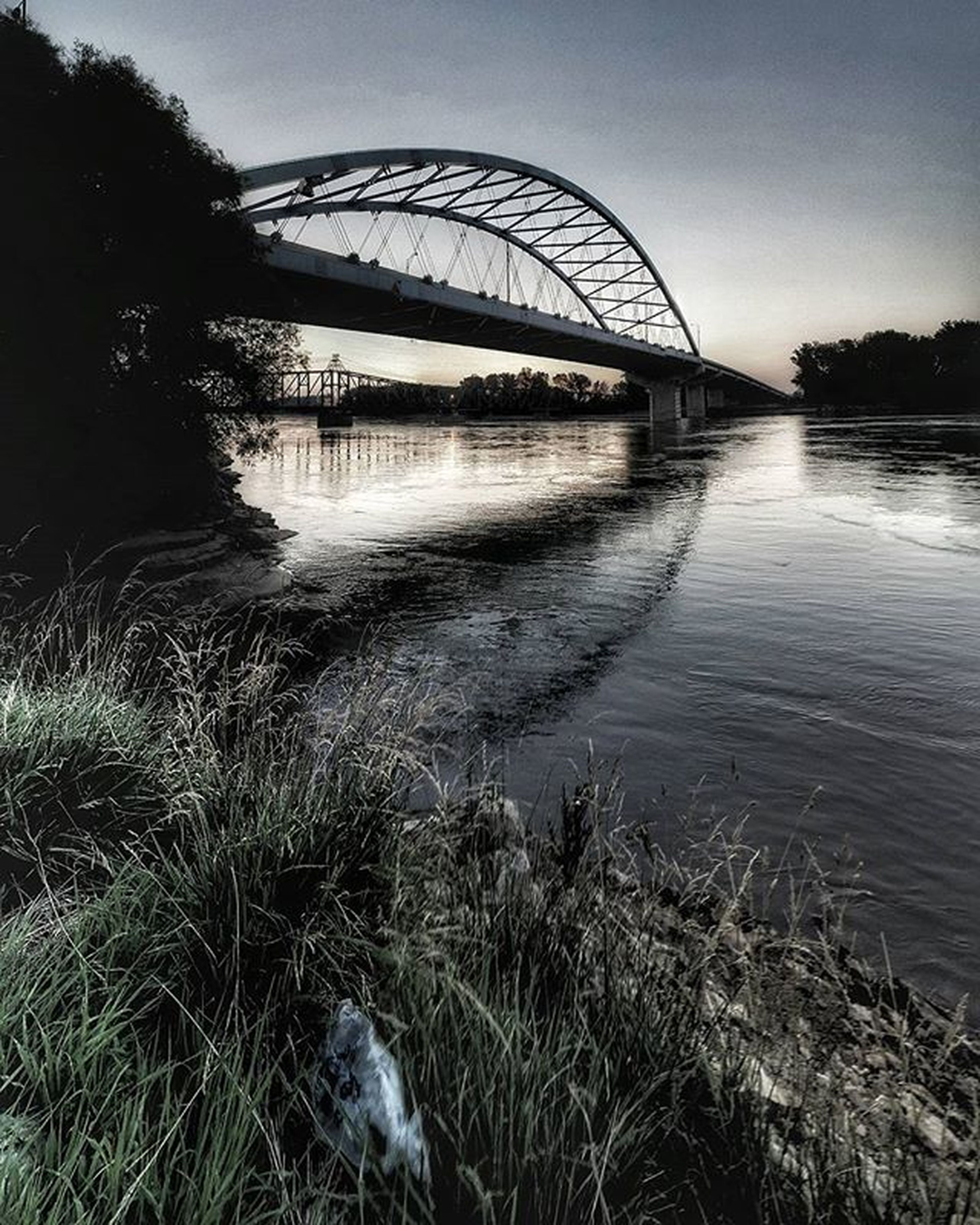 water, bridge - man made structure, river, connection, built structure, architecture, sky, engineering, bridge, clear sky, tree, arch bridge, reflection, grass, riverbank, arch, tranquility, nature, no people, lake