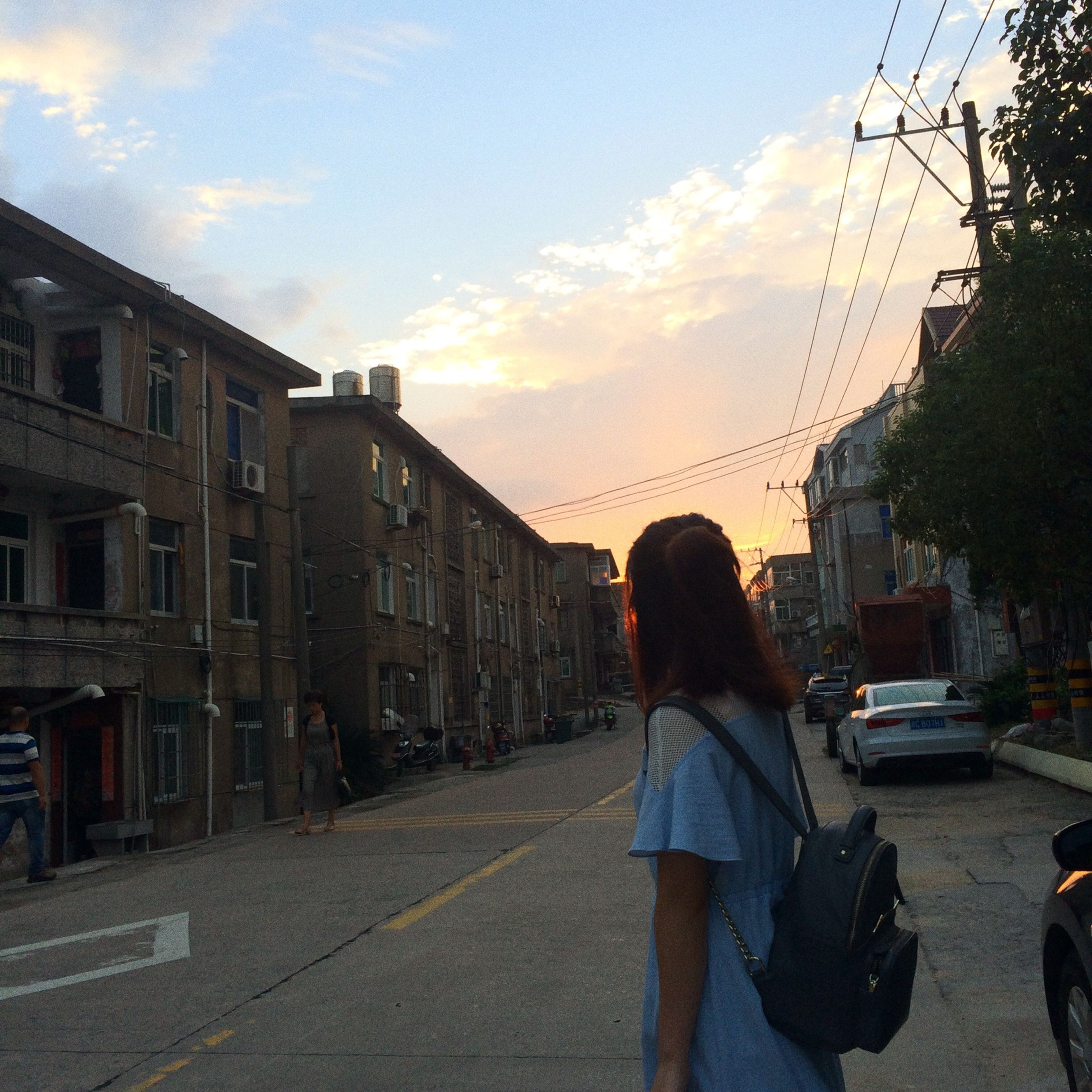 architecture, built structure, building exterior, sunset, sky, street, rear view, transportation, city, cloud, person, city life, outdoors, cloud - sky, the way forward, diminishing perspective, vanishing point