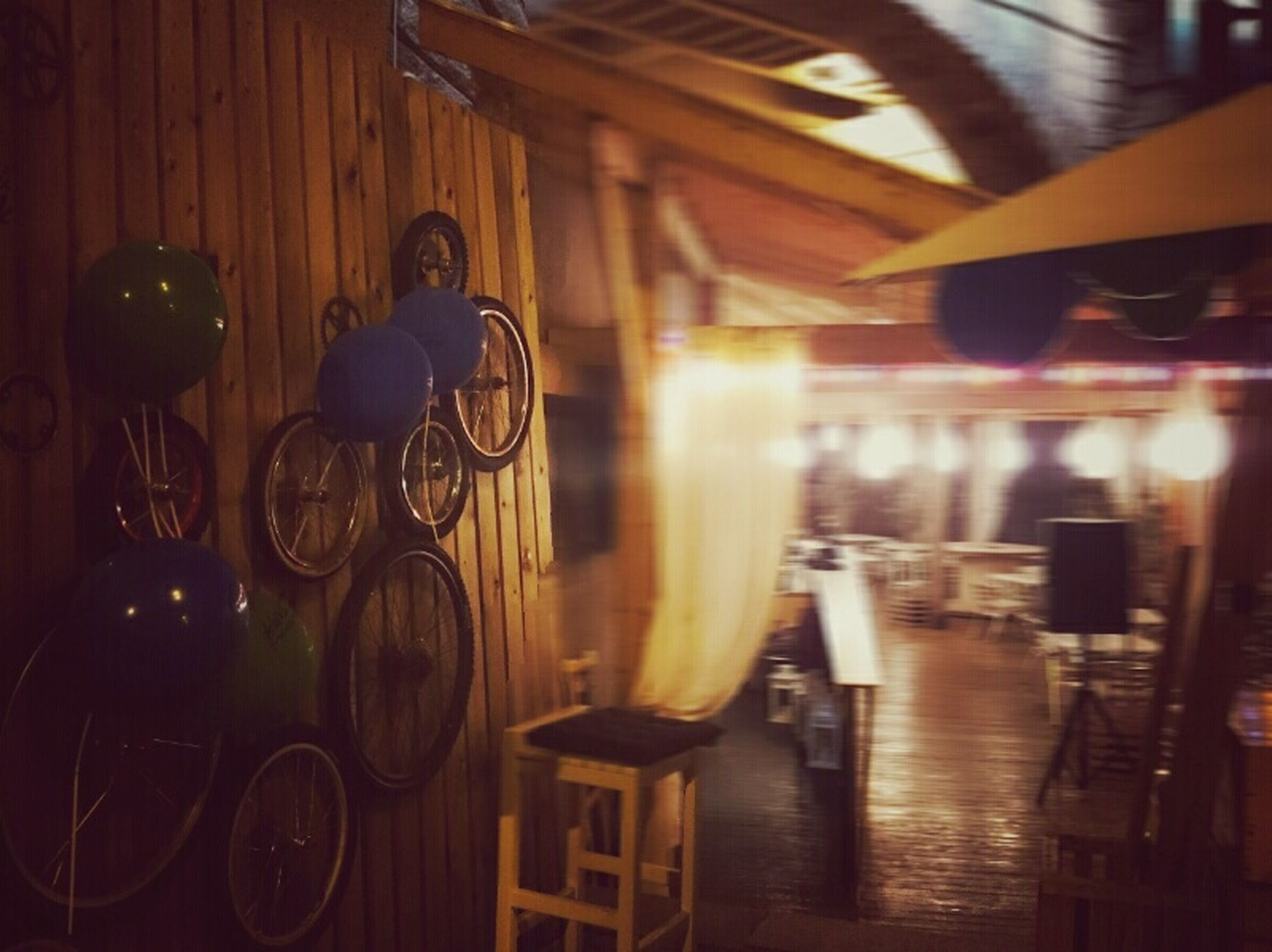 indoors, illuminated, lighting equipment, architecture, table, built structure, bicycle, in a row, chair, night, absence, no people, reflection, hanging, light - natural phenomenon, house, building exterior, shadow, sunlight, empty