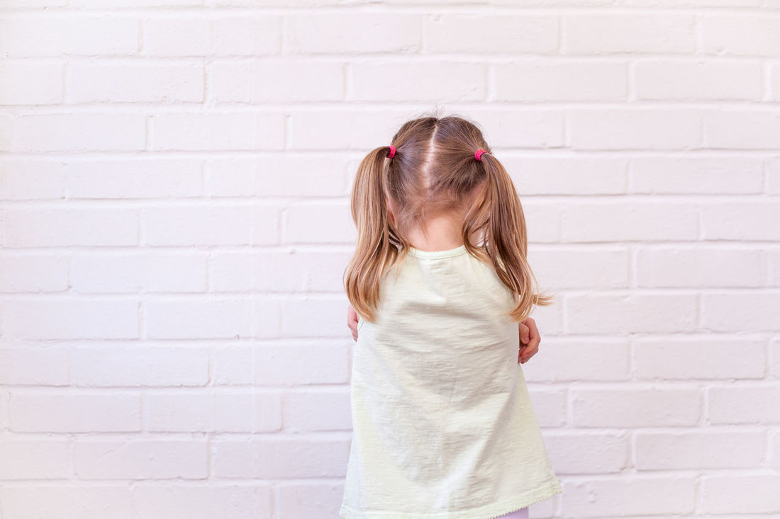 Female child with back to viewer and arms folded in grumpy or sad pose against white brick wall. Emotional or unhappy kid concept Angry Blond Hair Brick Wall Casual Clothing Child Childhood Children Only Day Elementary Age Eyeem People Female Female Model Girl Girls Long Hair Not Happy One Girl Only One Person Outdoors People Portrait Standing Sulking Upset White Color