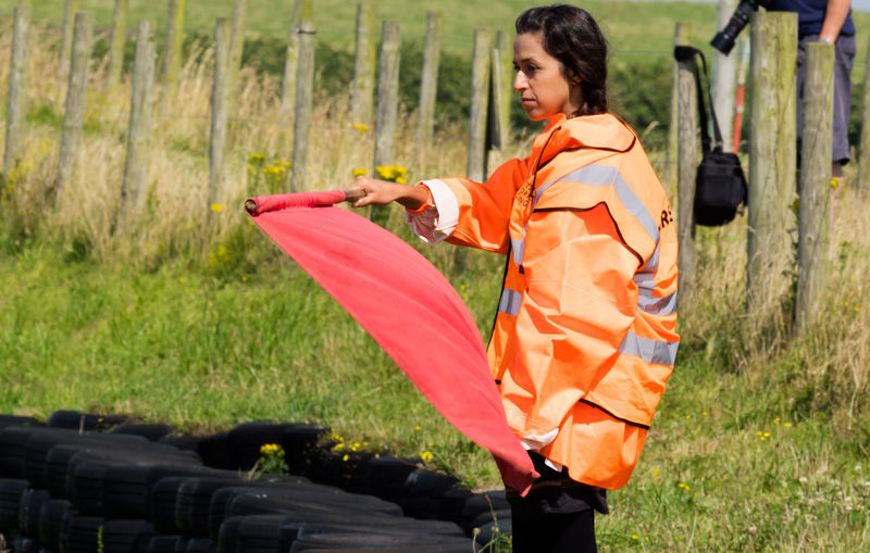 British Historic Motorcycle Racing, Trac Mon, Anglesey Adult Adults Only Danger Day Grass Growth Holding Leisure Activity Motor Cycle Racing Marshall Nature One Person Outdoors People Race Marshall Real People Red Flag Reflective Clothing Standing Women Young Adult