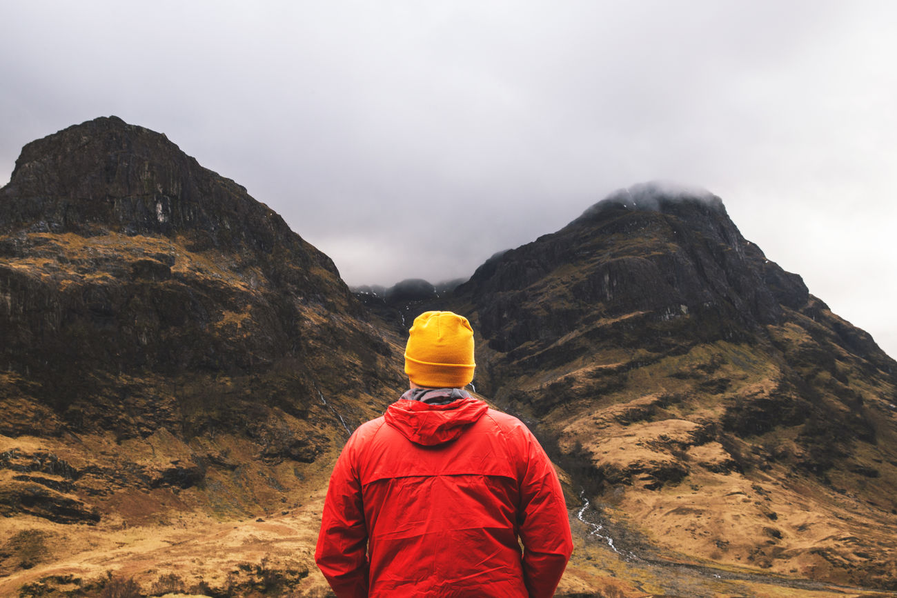 Man in mountains, Glencoe, Scotland Adventure Adventures Exploration Glencoe Hiking Landscape Man Moody Mountain Nature One Person Outdoors Rear View Red Scotland Scottish Highlands Sky Standing Walking
