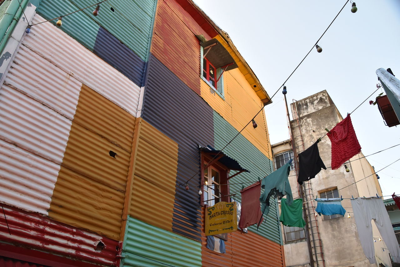 flag, building exterior, built structure, architecture, low angle view, clothesline, hanging, patriotism, outdoors, day, drying, textile, multi colored, bunting, city, no people